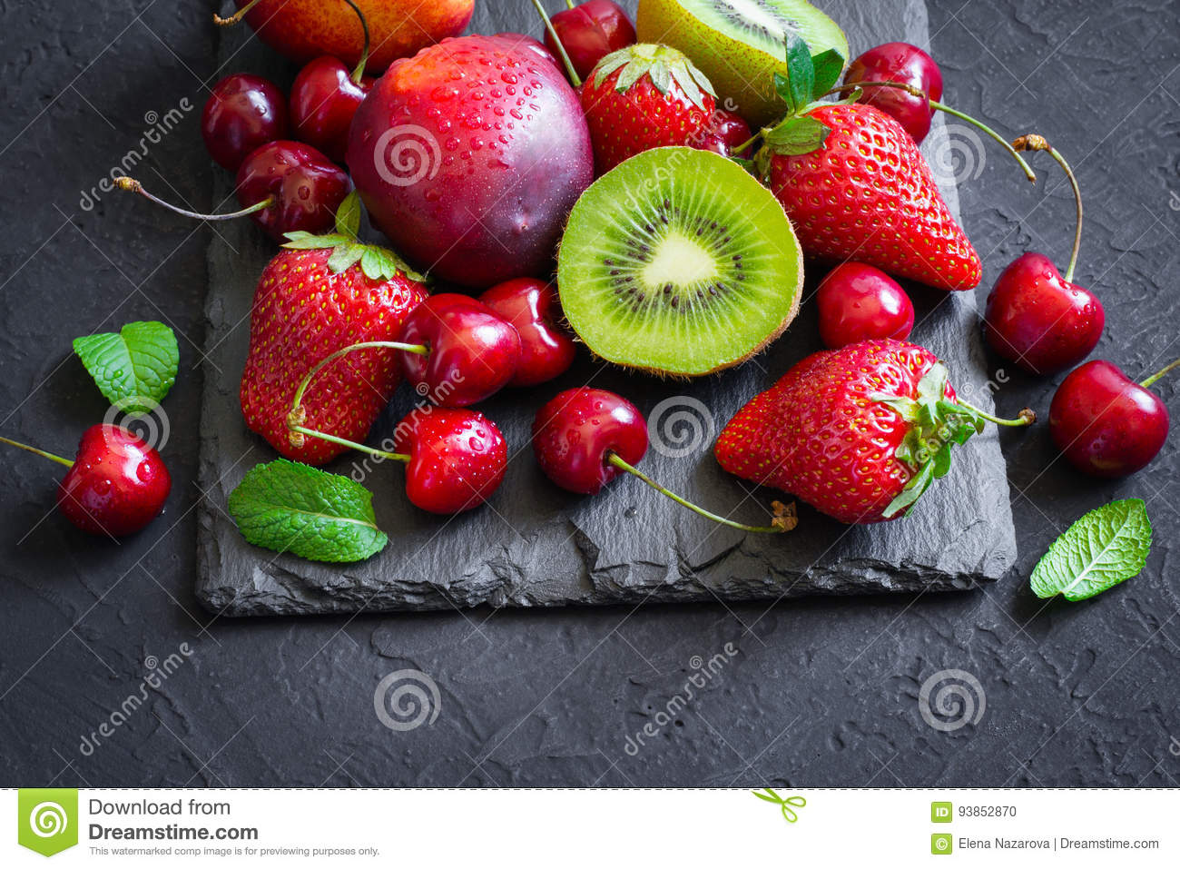 Assorted of Juicy summer fruits and berries. Strawberry, cherry, kiwi and peaches on black slate plate.