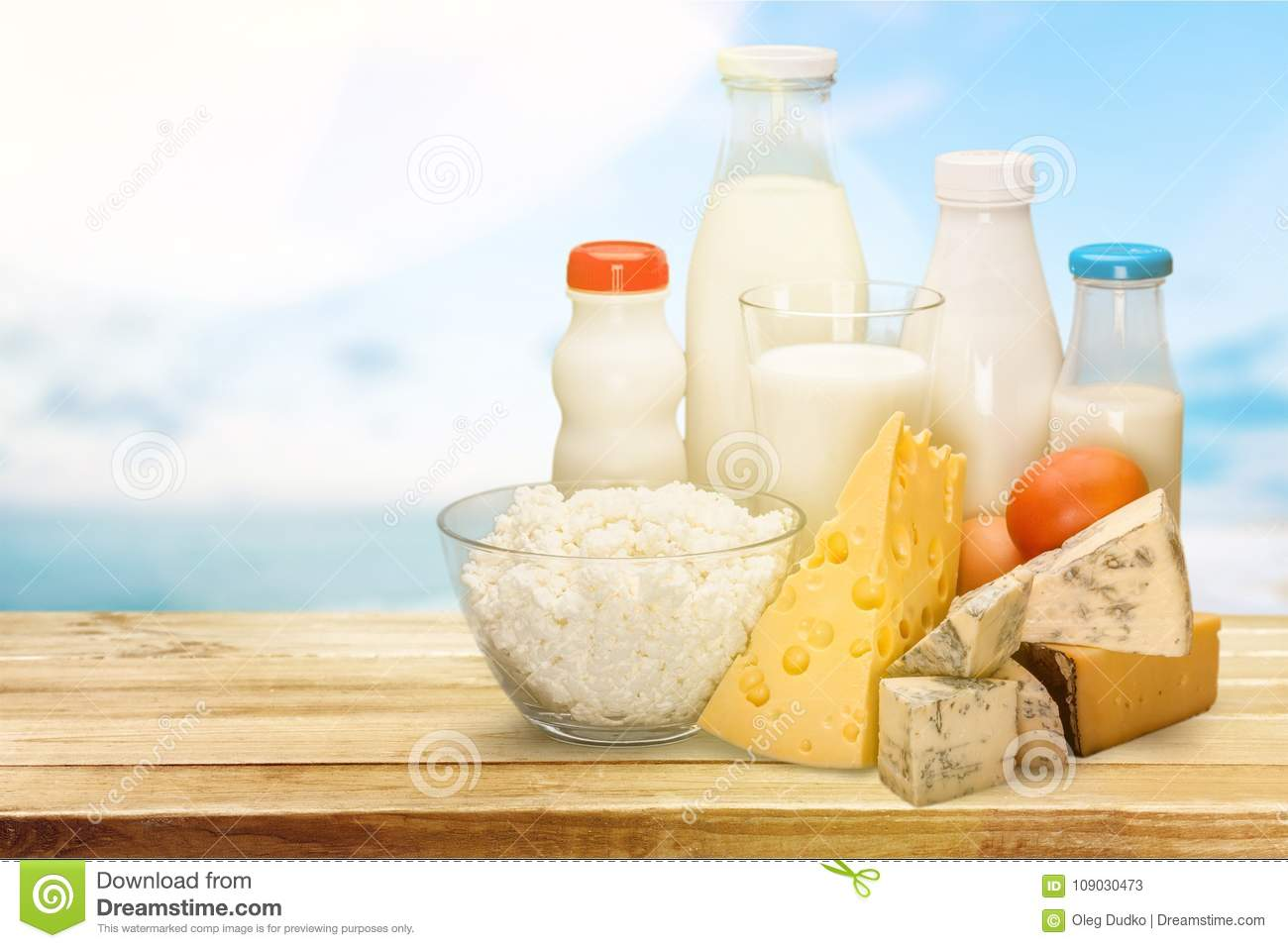 Assorted milk products on wooden table on natural