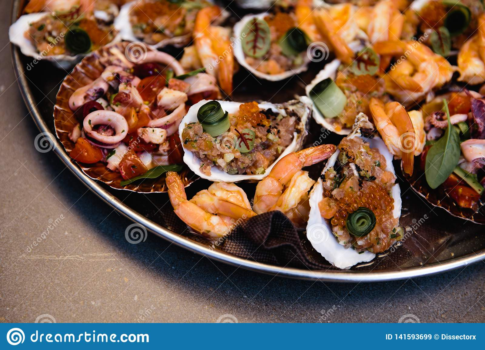 Assorted seafood, mussels, squid, scallops, salmon fillet and tiger shrimps with garlic creamy sauce, parmesan cheese