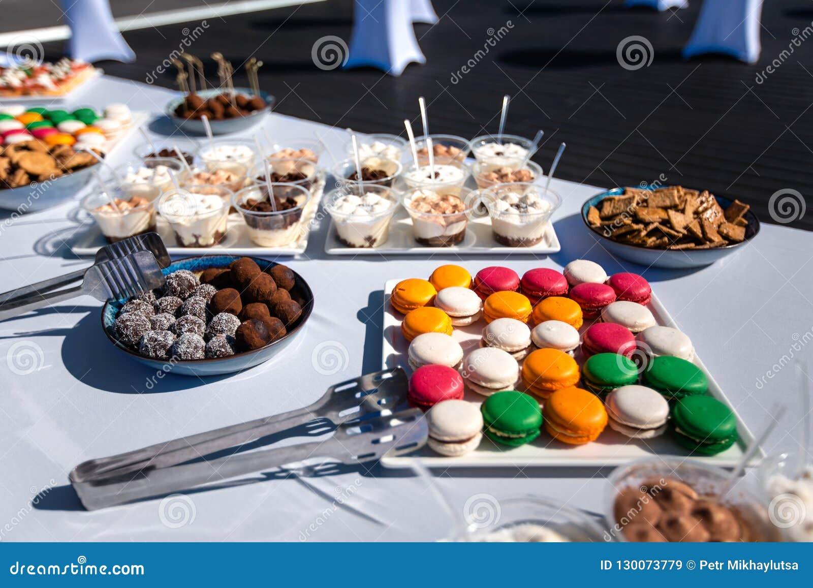 Assortiment des apéritifs savoureux - canapes, biscuits sur la nappe blanche