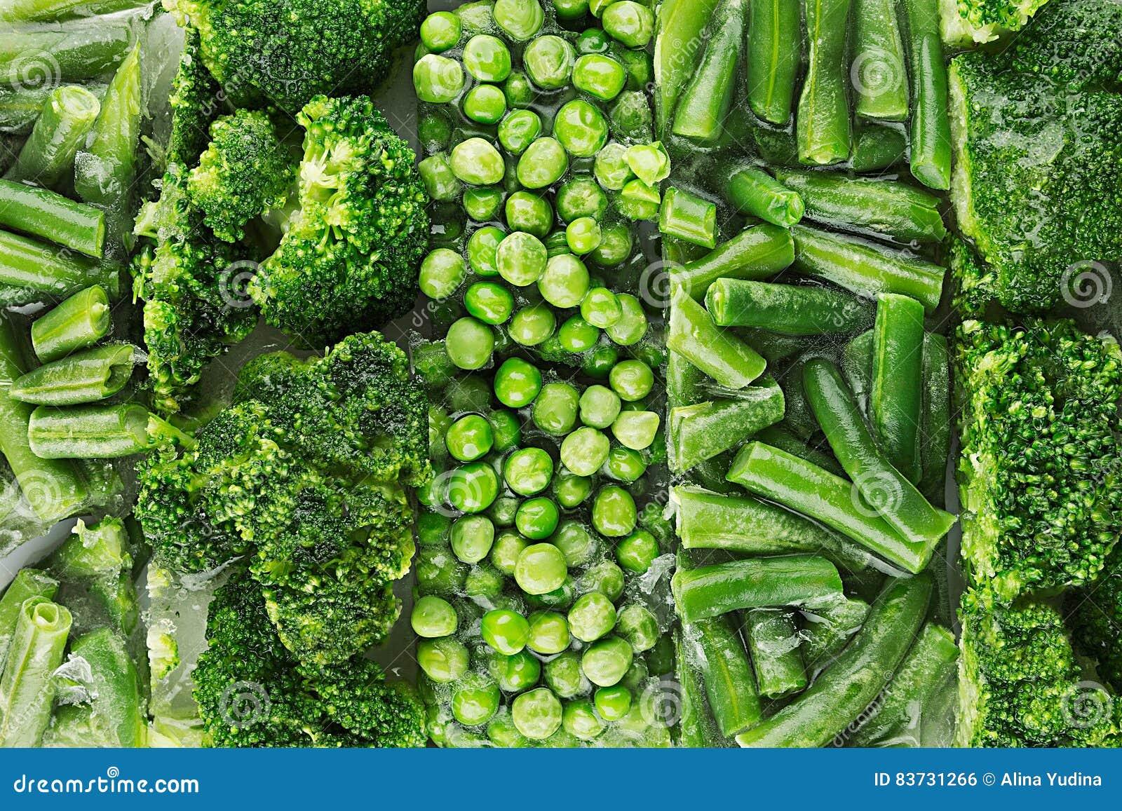 Assortimento dei piselli congelati freschi, fagiolino, broccoli con il primo piano di brina come fondo