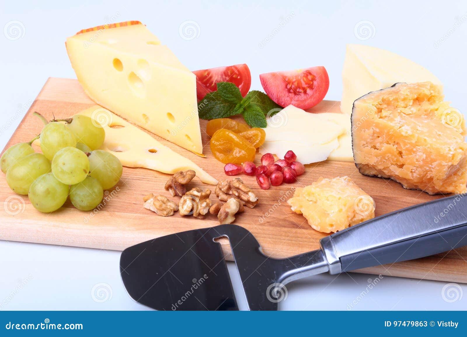 Assortimento di formaggio con i frutti, l uva, i dadi ed il coltello del formaggio su un vassoio di legno del servizio