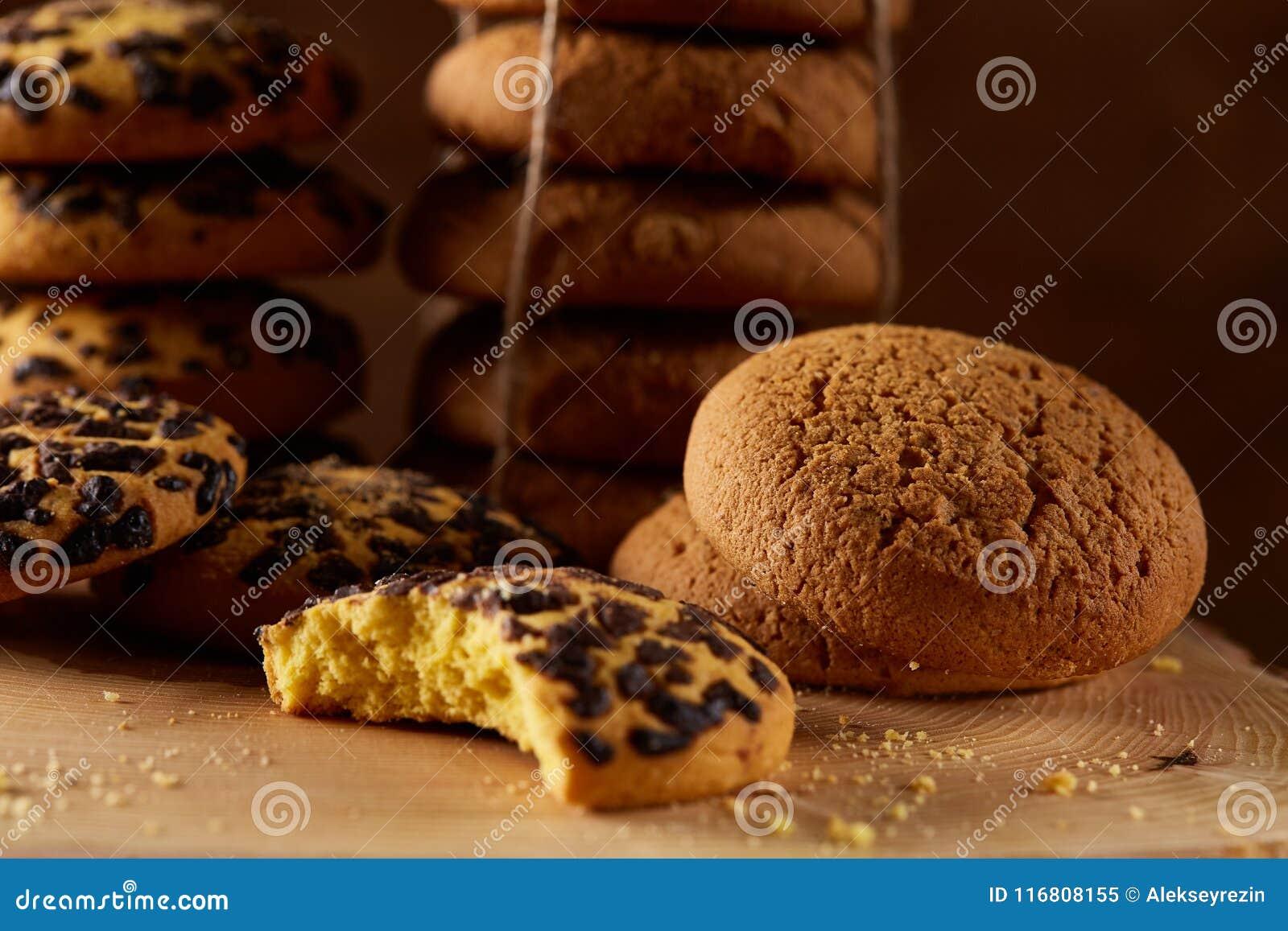 Assortimento dolce dei biscotti su un ceppo di legno rotondo sopra fondo di legno rustico, primo piano, fuoco selettivo