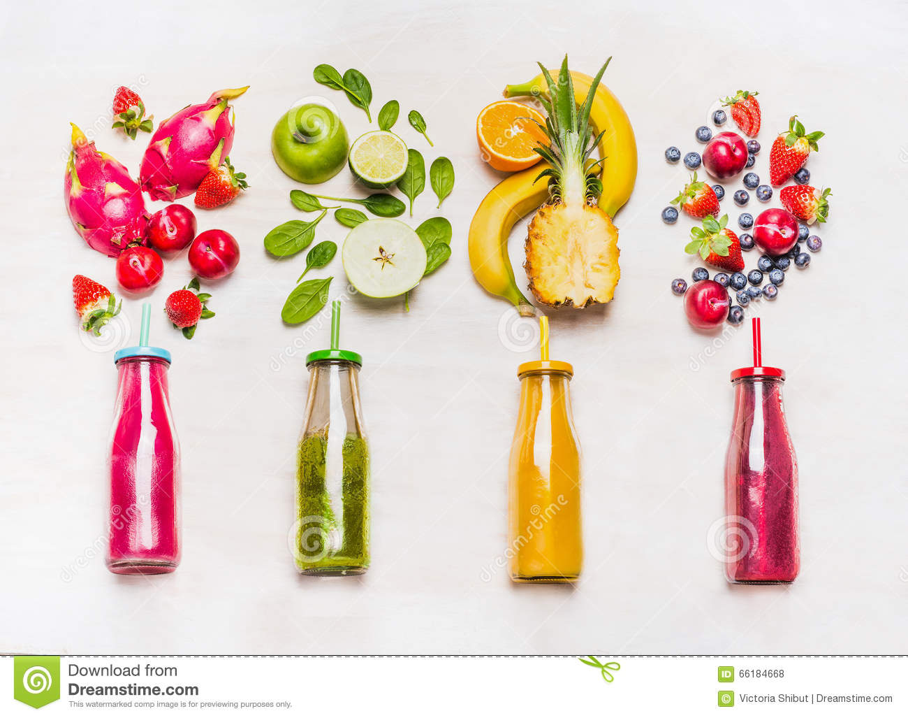 Assortment of fruit and vegetables smoothies in glass bottles with straws on white wooden background.