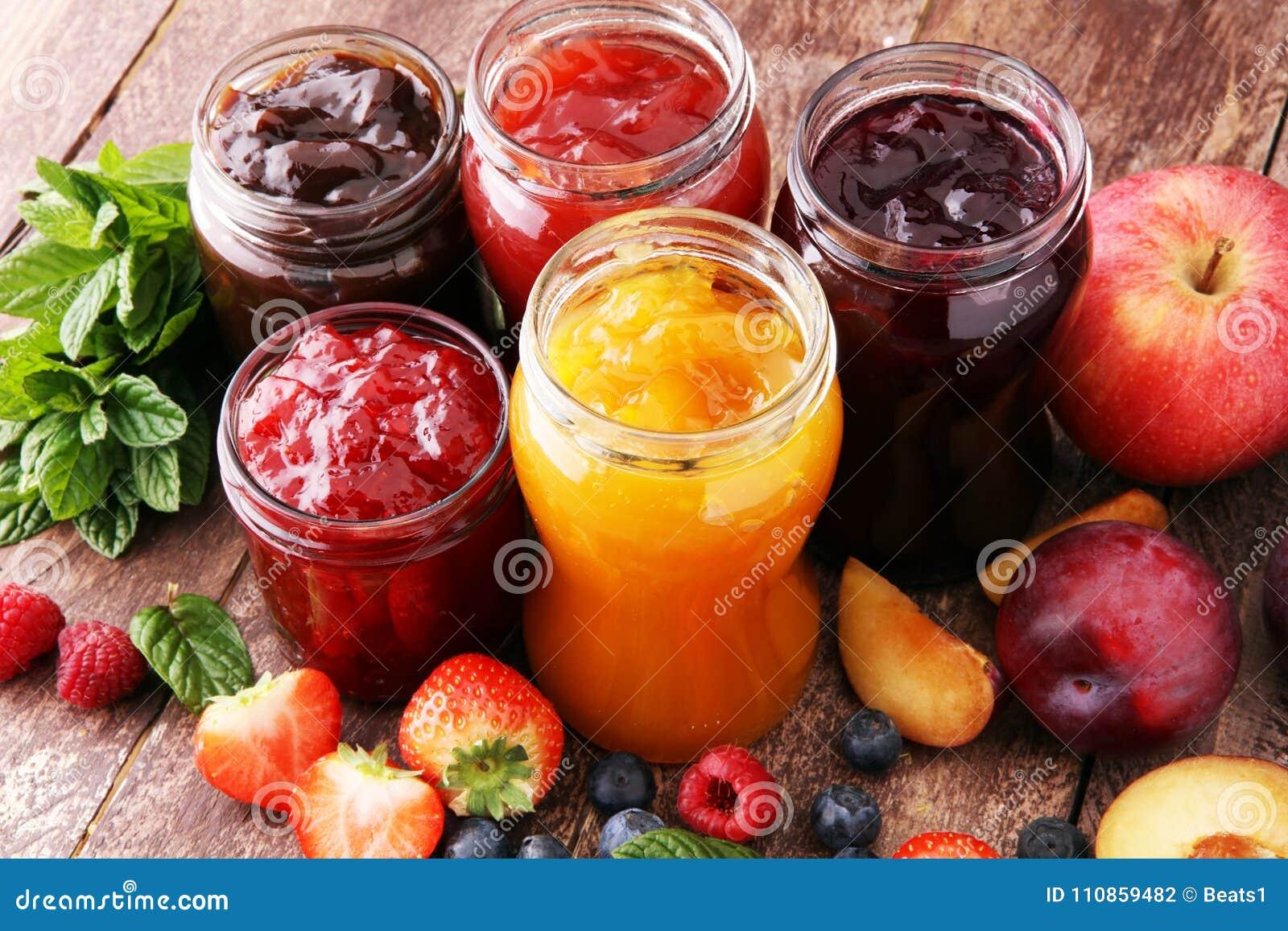 Assortment of jams, seasonal berries, plums, mint and fruits.