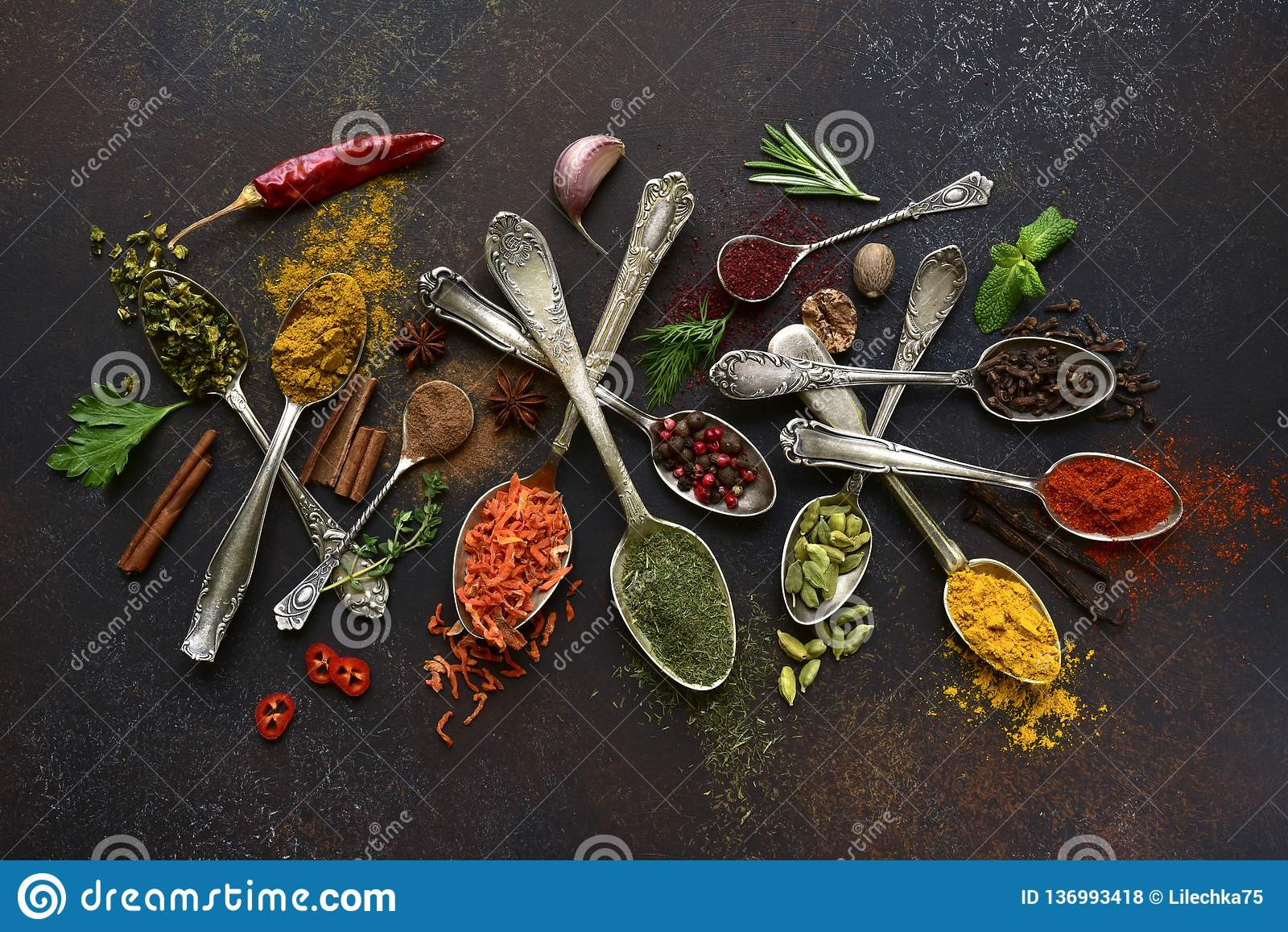 Assortment of natural spices on a vintage spoons.Top view with copy space. Assortment of natural spices on a vintage spoons over dark slate, stone, concrete or royalty free stock photos