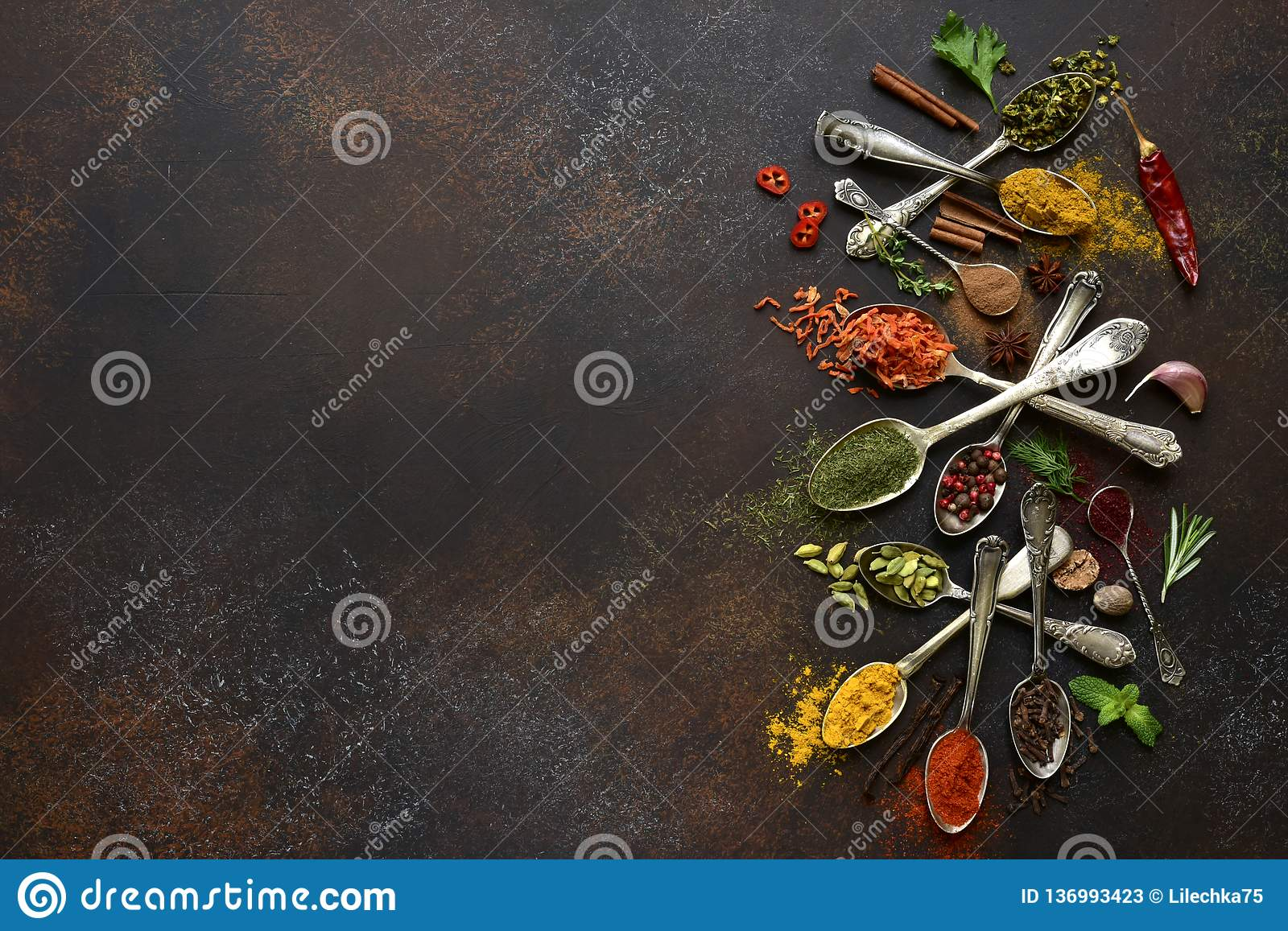 Assortment of natural spices on a vintage spoons.Top view with copy space. Assortment of natural spices on a vintage spoons over dark slate, stone, concrete or stock photos