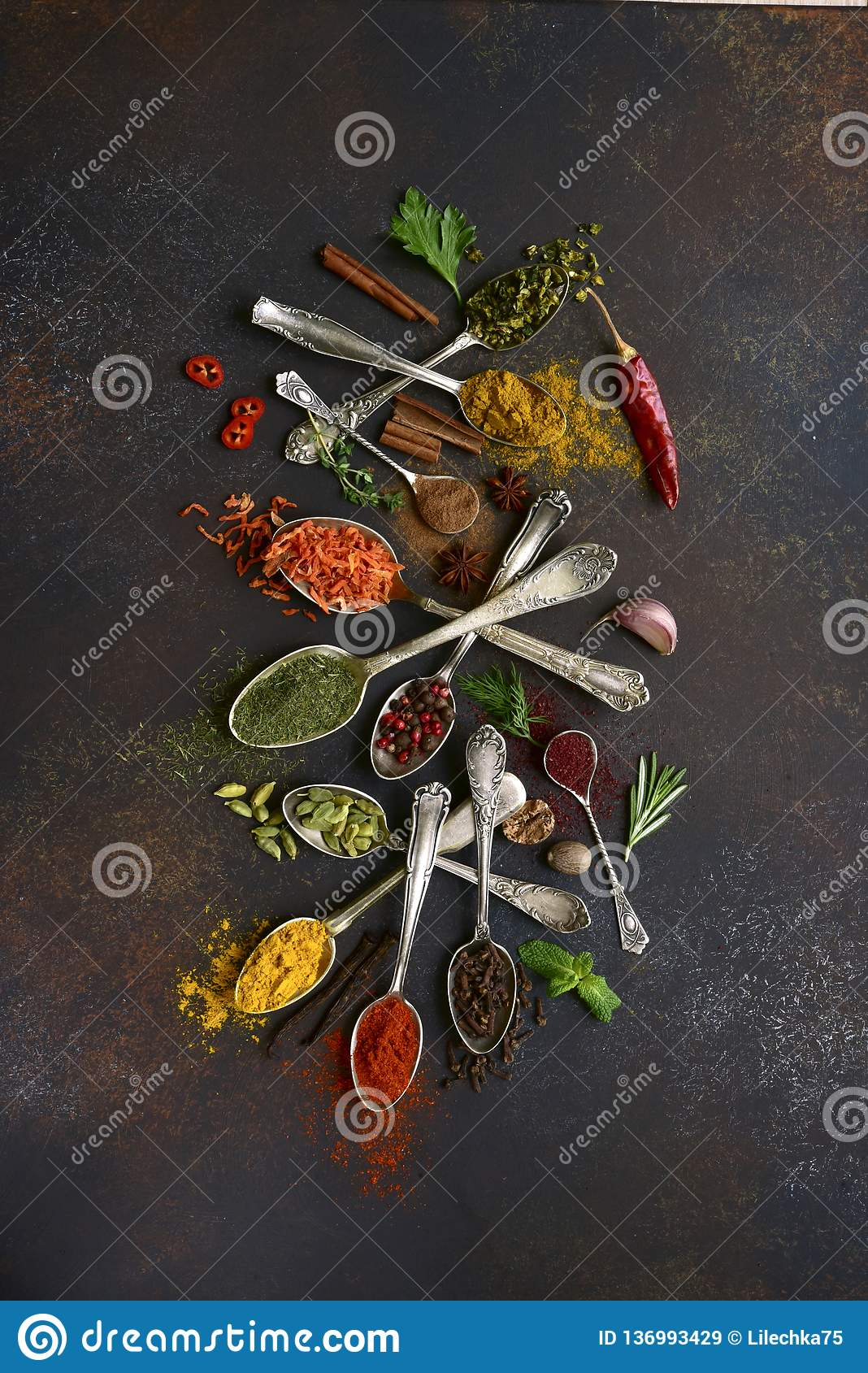 Assortment of natural spices on a vintage spoons.Top view with copy space. Assortment of natural spices on a vintage spoons over dark slate, stone, concrete or royalty free stock images