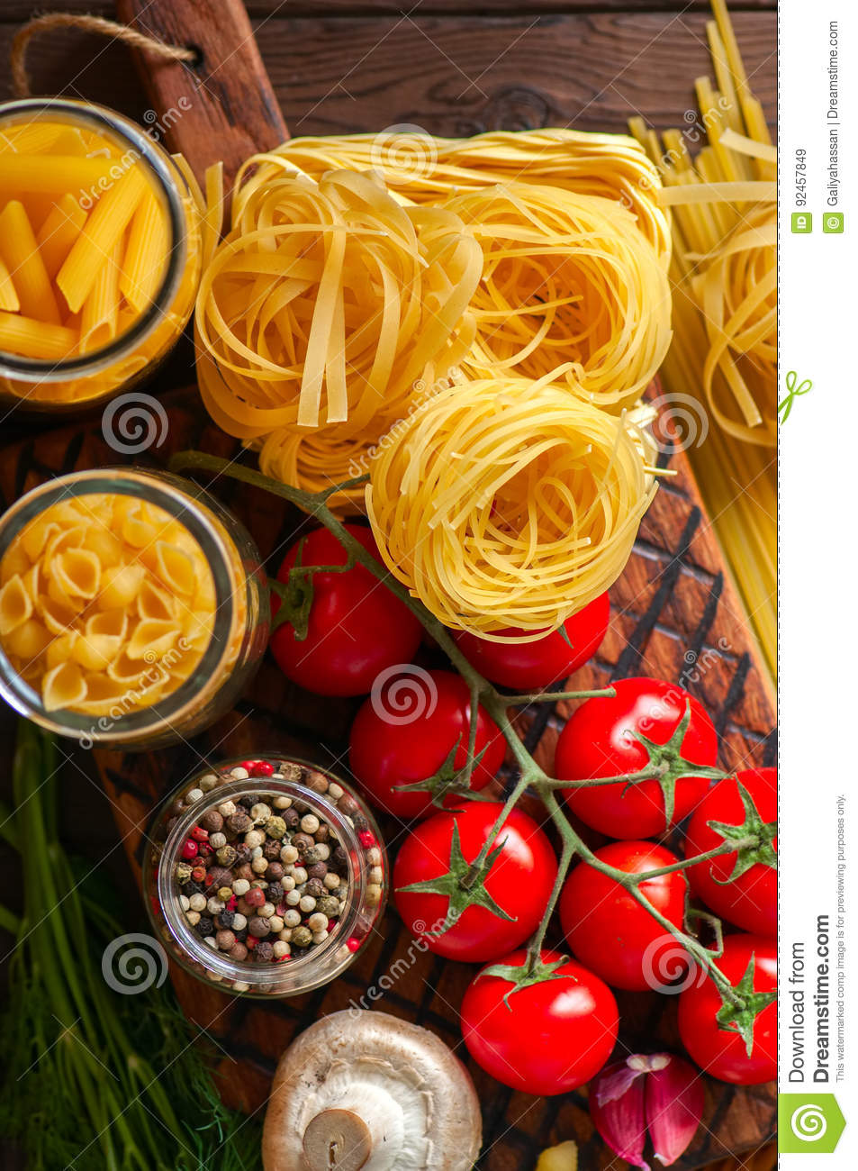Assortment of raw types and shapes of italian pasta and wooden b