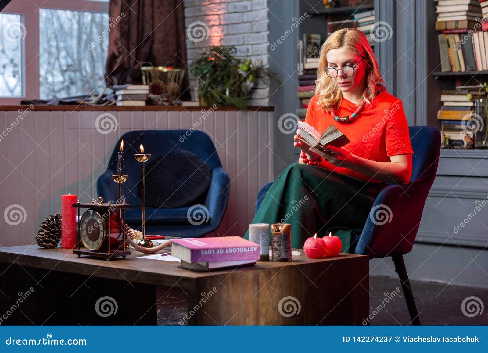 Astrologist elegante que se sienta en la sala de estar y que lee el libro de la astrología