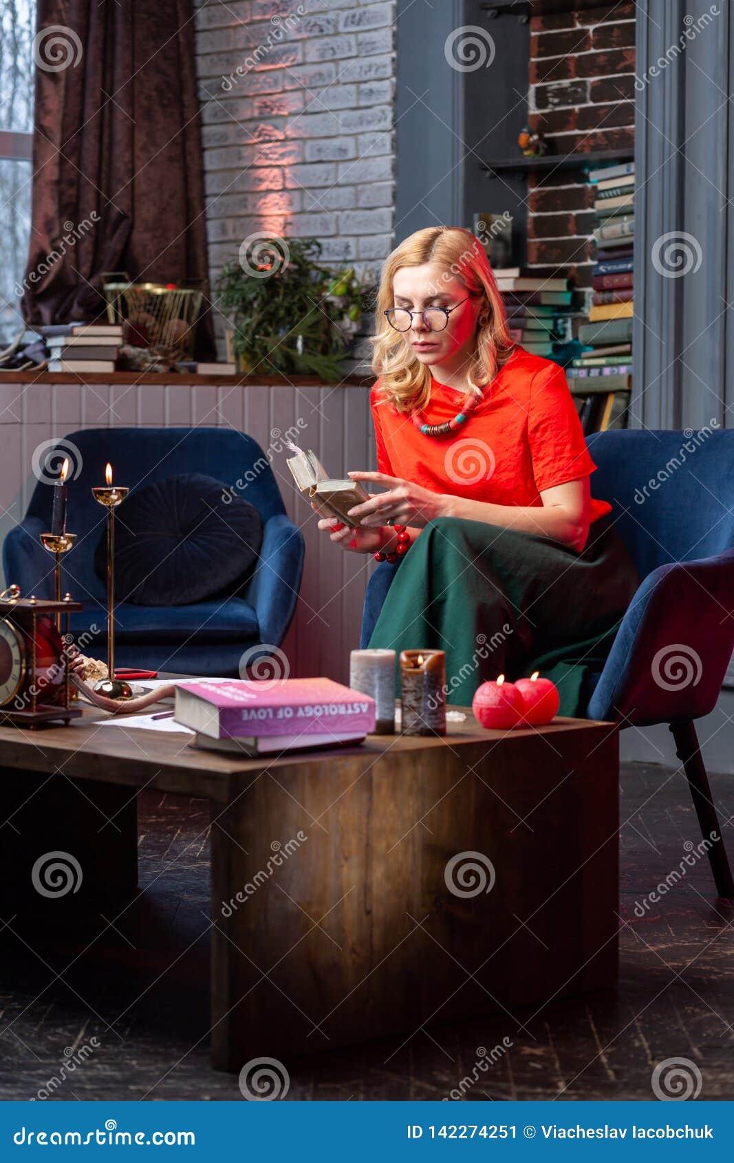 Astrologist hermoso elegante que disfruta de tiempo de la uno mismo-educación en casa