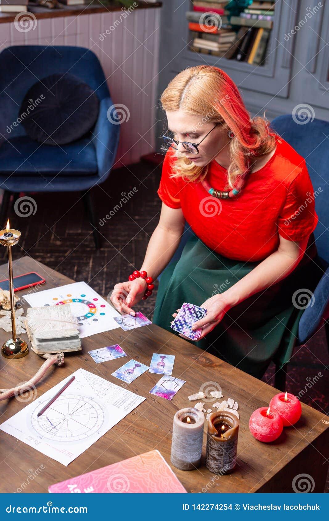 Astrologist maduro que senta-se na poltrona e na previsão futura praticando