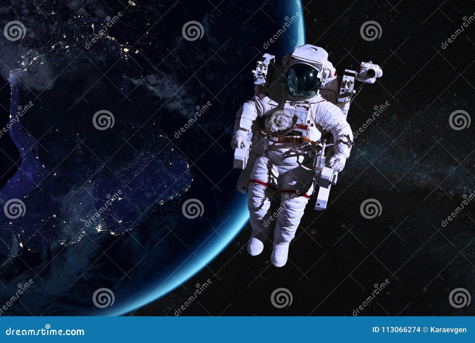 Astronauta en espacio exterior en el fondo de la tierra de la noche