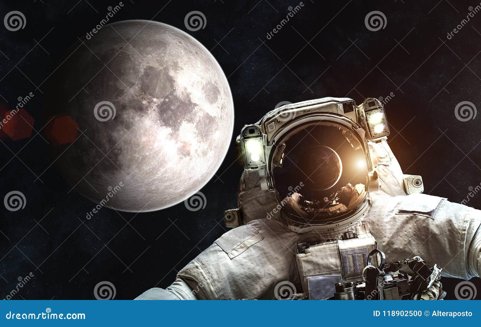 Astronaute sur le fond de la lune Sun et terre par réflexion de casque de la combinaison spatiale Des éléments de l image sont fo