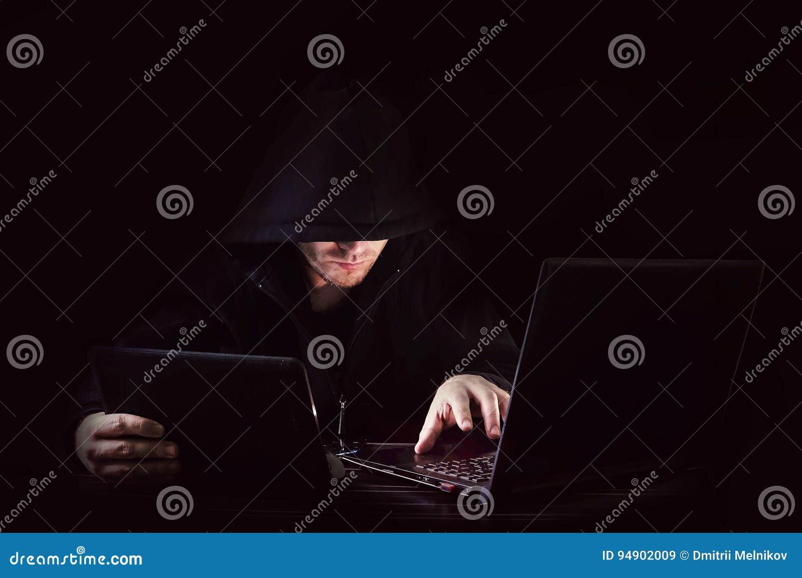 Ataque cibernético con el pirata informático encapuchado irreconocible