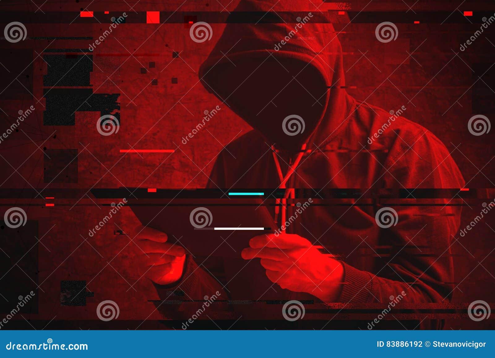 Ataque cibernético con el pirata informático encapuchado irreconocible que usa los comp de la tableta