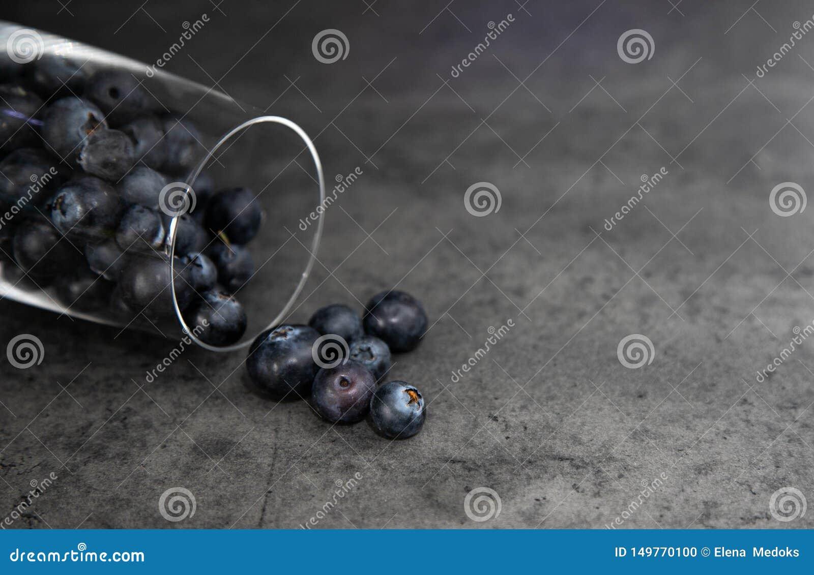 Atasco de cereza en un tarro de cristal con una tapa abierta del color rojo y blanco en un tablero de madera, tablero Fondo gris