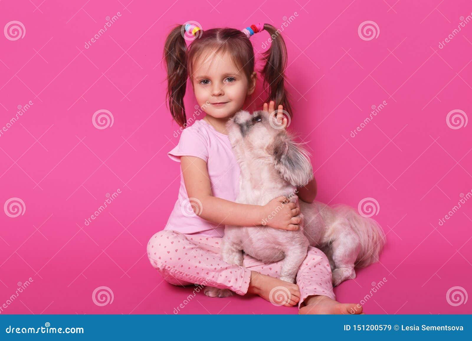 Atelieraufnahme des kleinen lustigen Kindes, das auf Boden, betrachtend direkt der Kamera sitzt und umarmen ihr Haustier, Hund, d