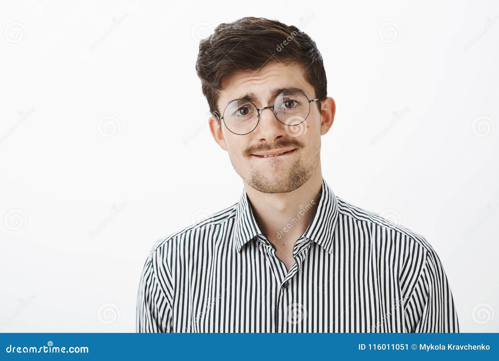 Atelieraufnahme des nervösen ungewissen lustigen bärtigen Kerls, in den runden Gläsern, in beißender Lippe und etwas in die Stirn
