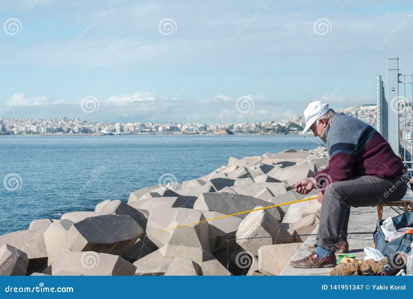 Aten Grekland December 16 Fiskaren 2018 fångar fisken från vågbrytaren
