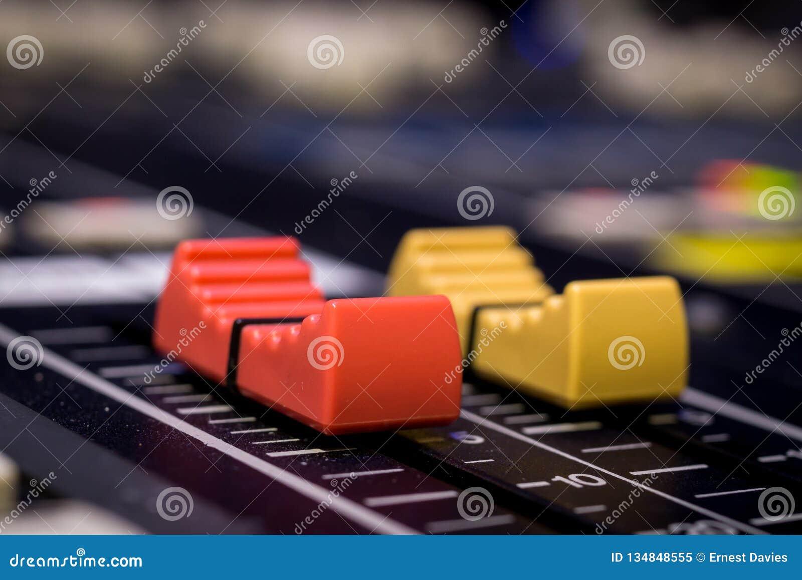 Atenuadores rojos y amarillos de la consola de mezcla audio profesional
