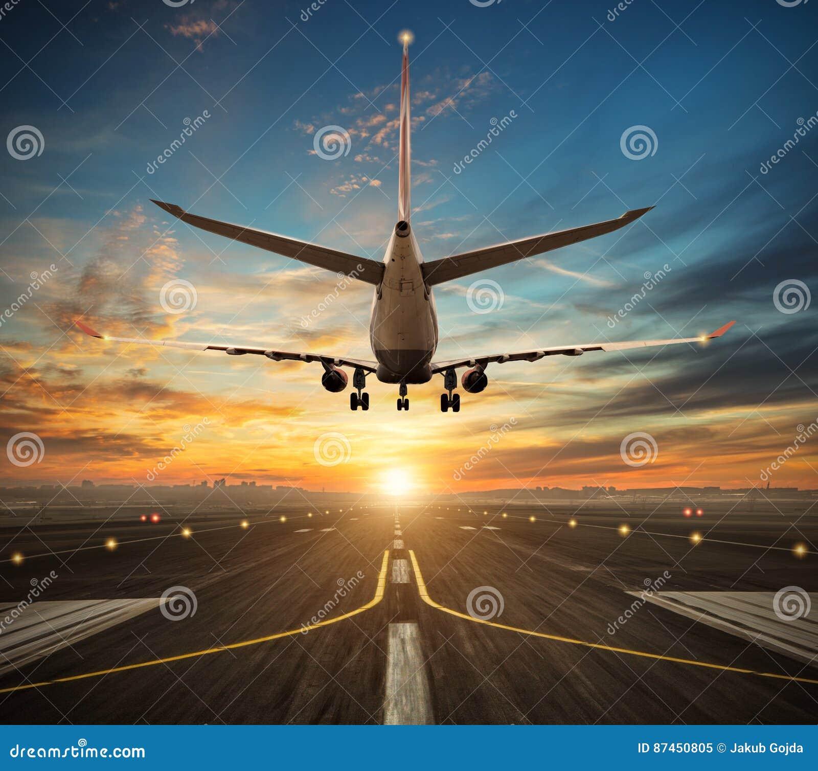 Aterrissagem de avião à pista de decolagem do aeroporto na luz do por do sol