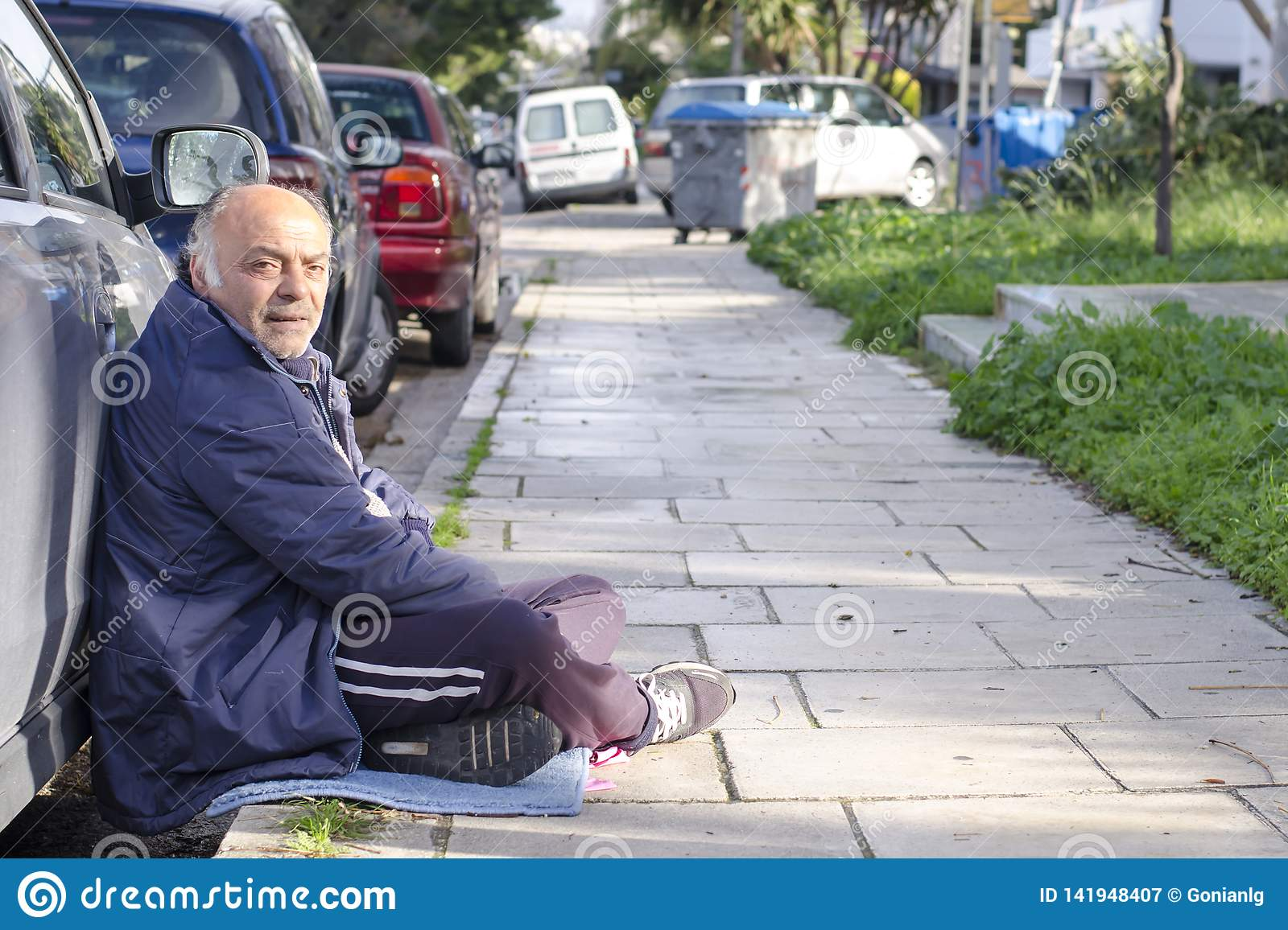 Athens, Greece / December 17,2018 Beggar asks for alms on the streets of Athens along the road cluttered with cars