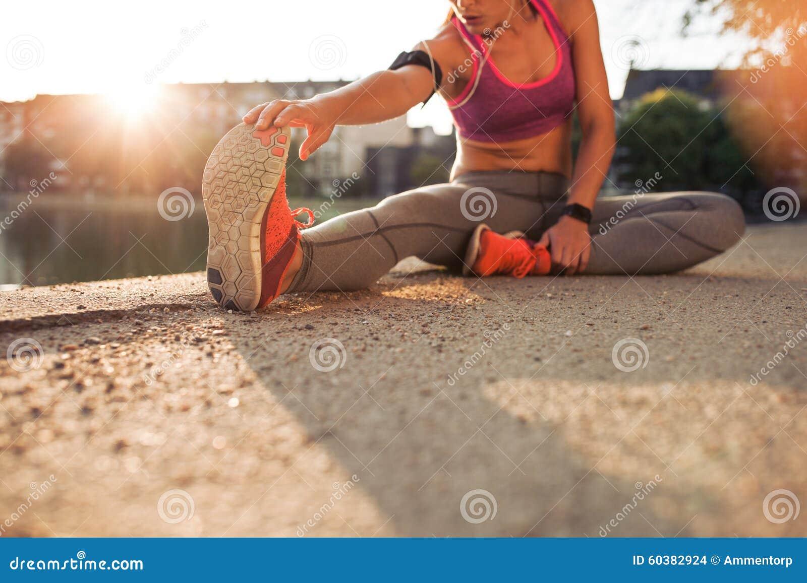Athlète féminin étirant des jambes