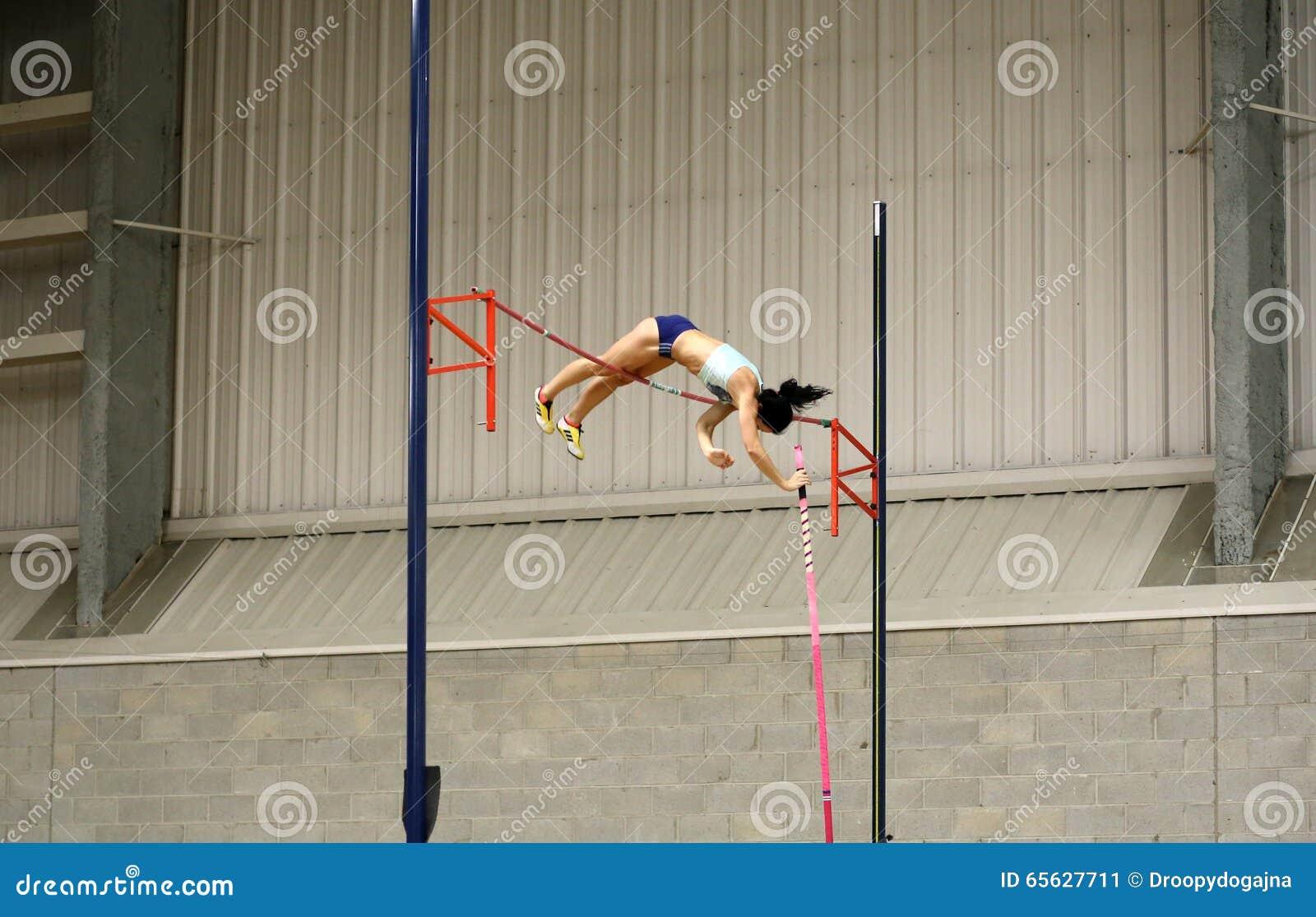 Athlète féminin concurrençant dans la chambre forte de poteau
