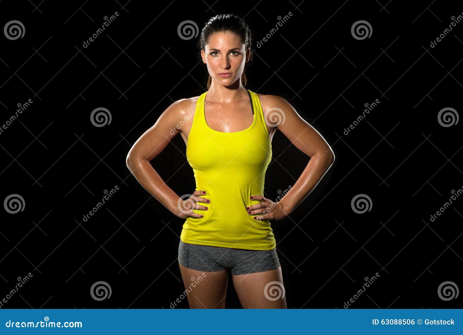 Athlète modifié la tonalité mince mince de corps féminin d ajustement attrayant d isolement sur le noir tenant avec confiance la