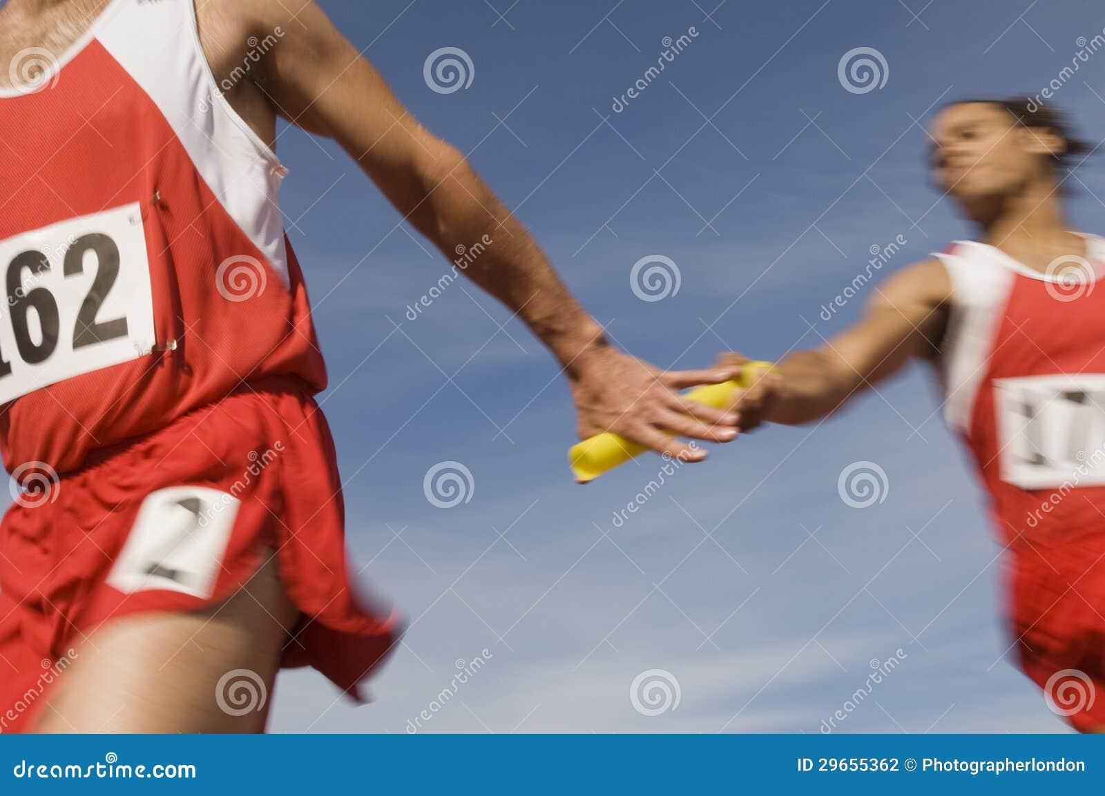 Athlètes passant le bâton dans la course de relais