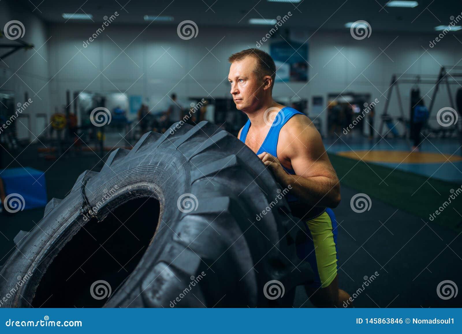 Athl?te faisant l exercice avec le pneu de camion, crossfit
