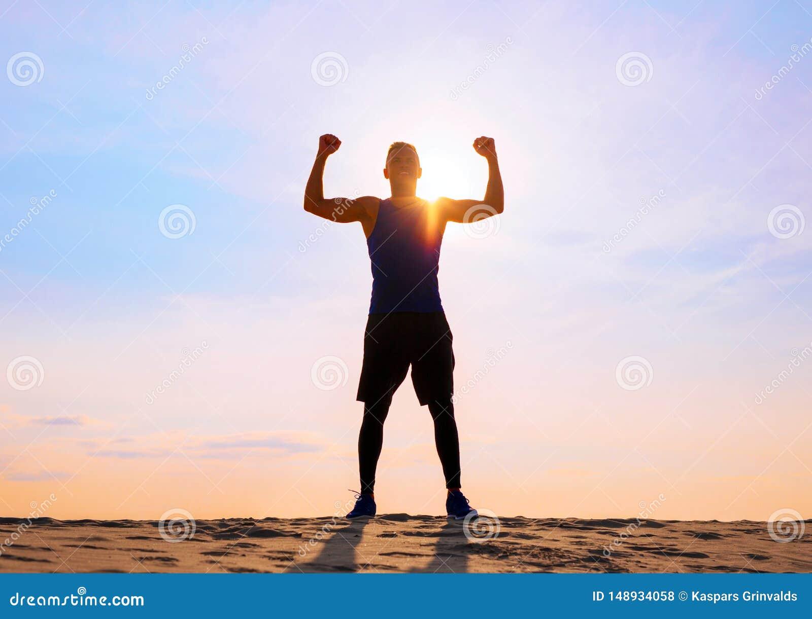 Athl?te masculin de forme physique avec des bras vers le haut de c?l?brer le succ?s et les buts
