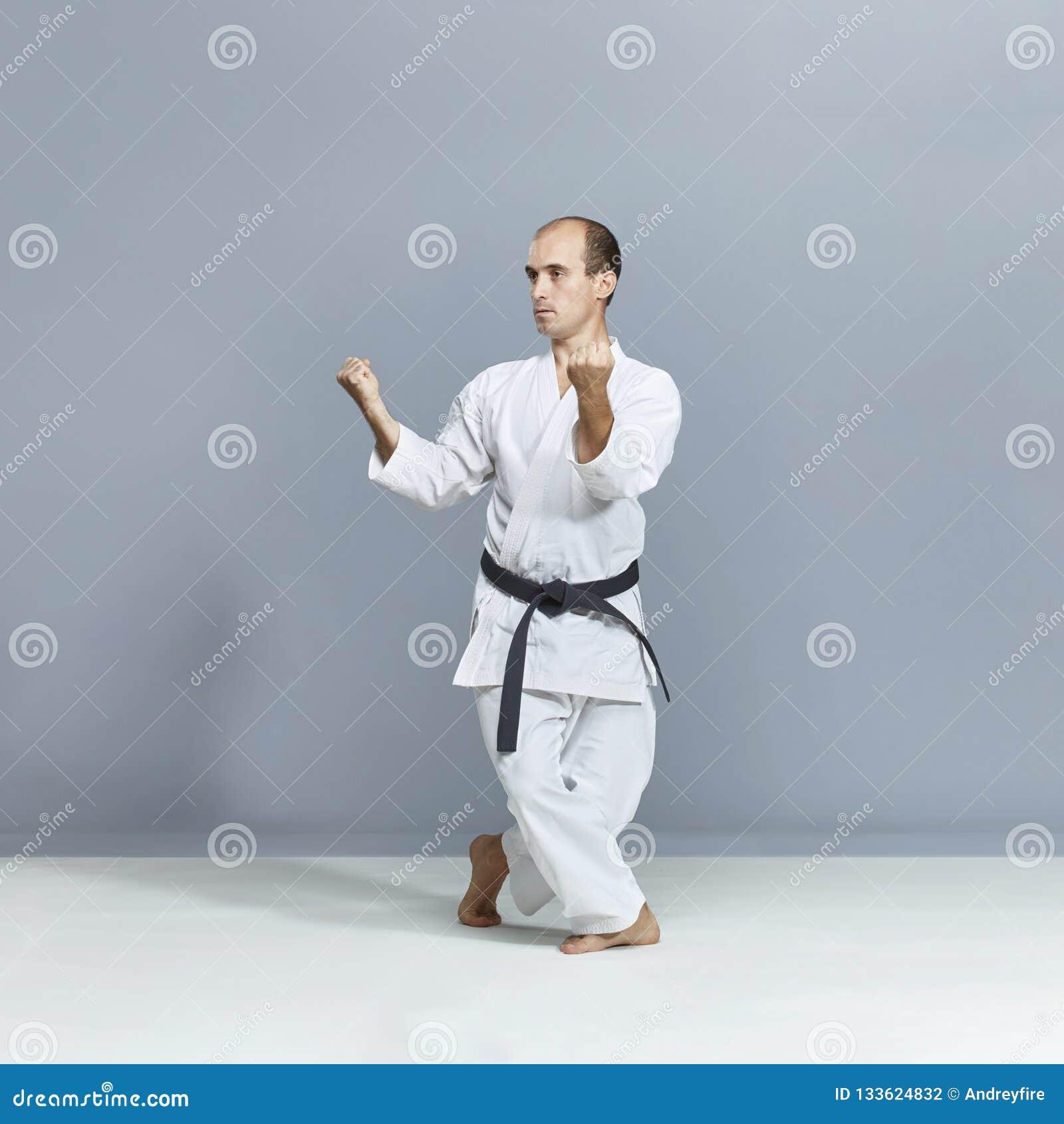 Athlet mit einem schwarzen Gürtel und einem weißen karategi bildet formal Karateübungen aus
