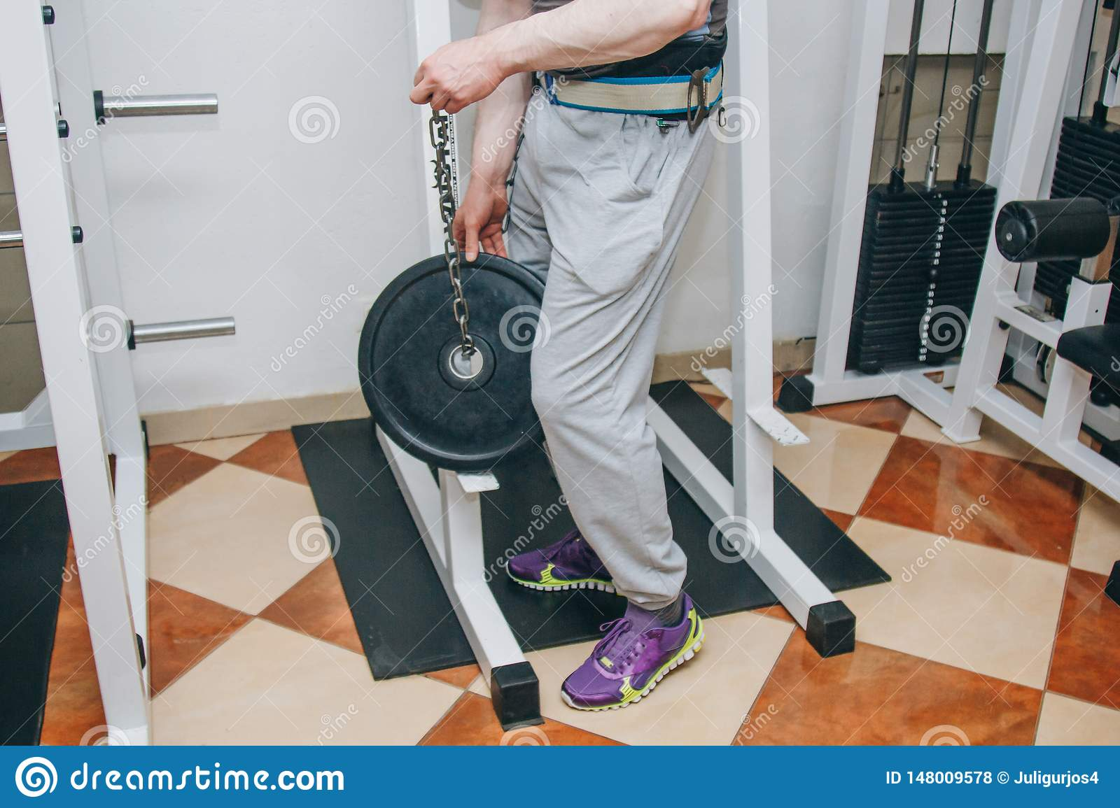 Athlete doing exercise with weight on the waist belt in the center of training. training tools in the gym close-up