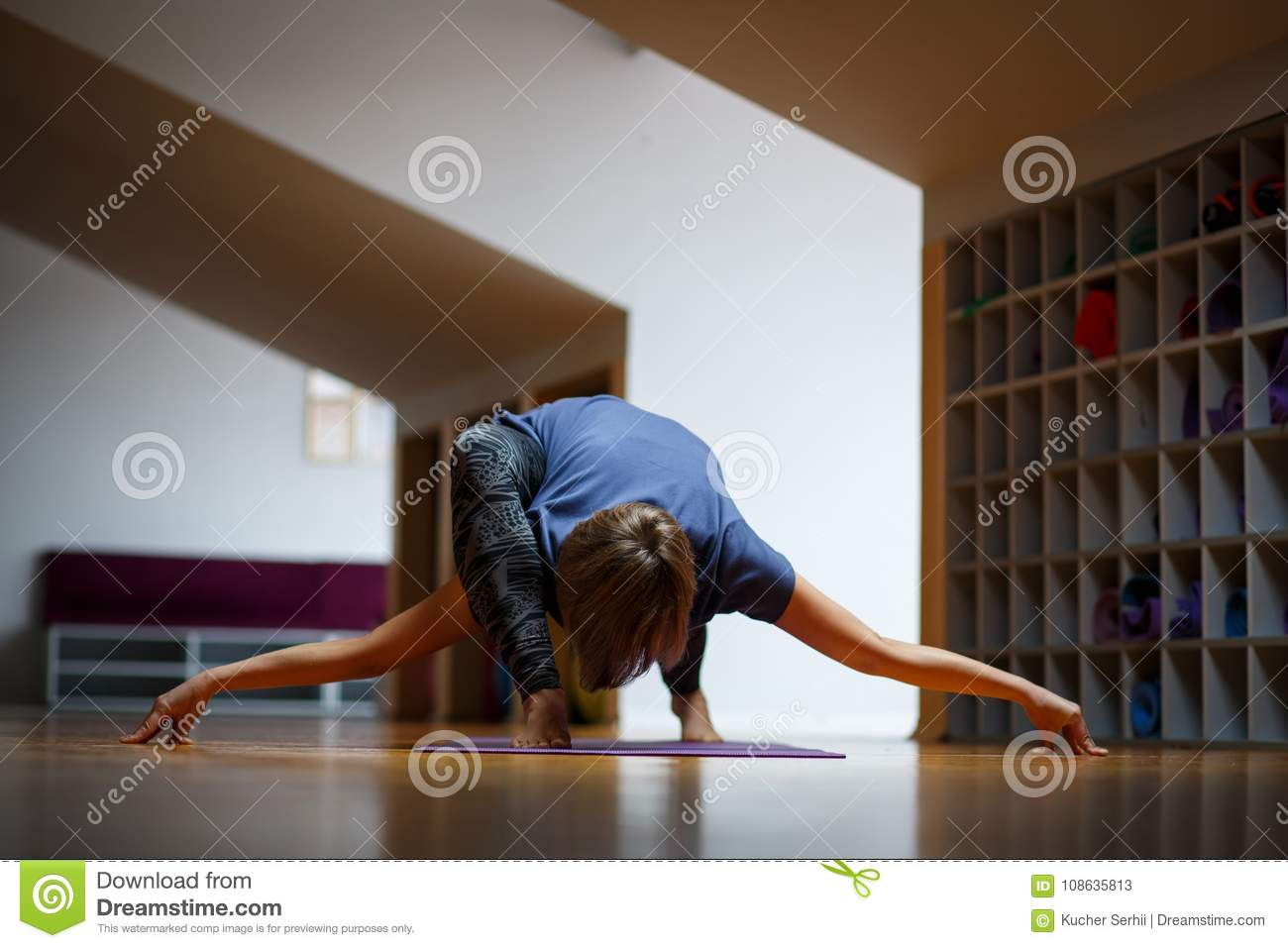 An Athlete Girl Makes Incredible Yoga Exercises In The Gym