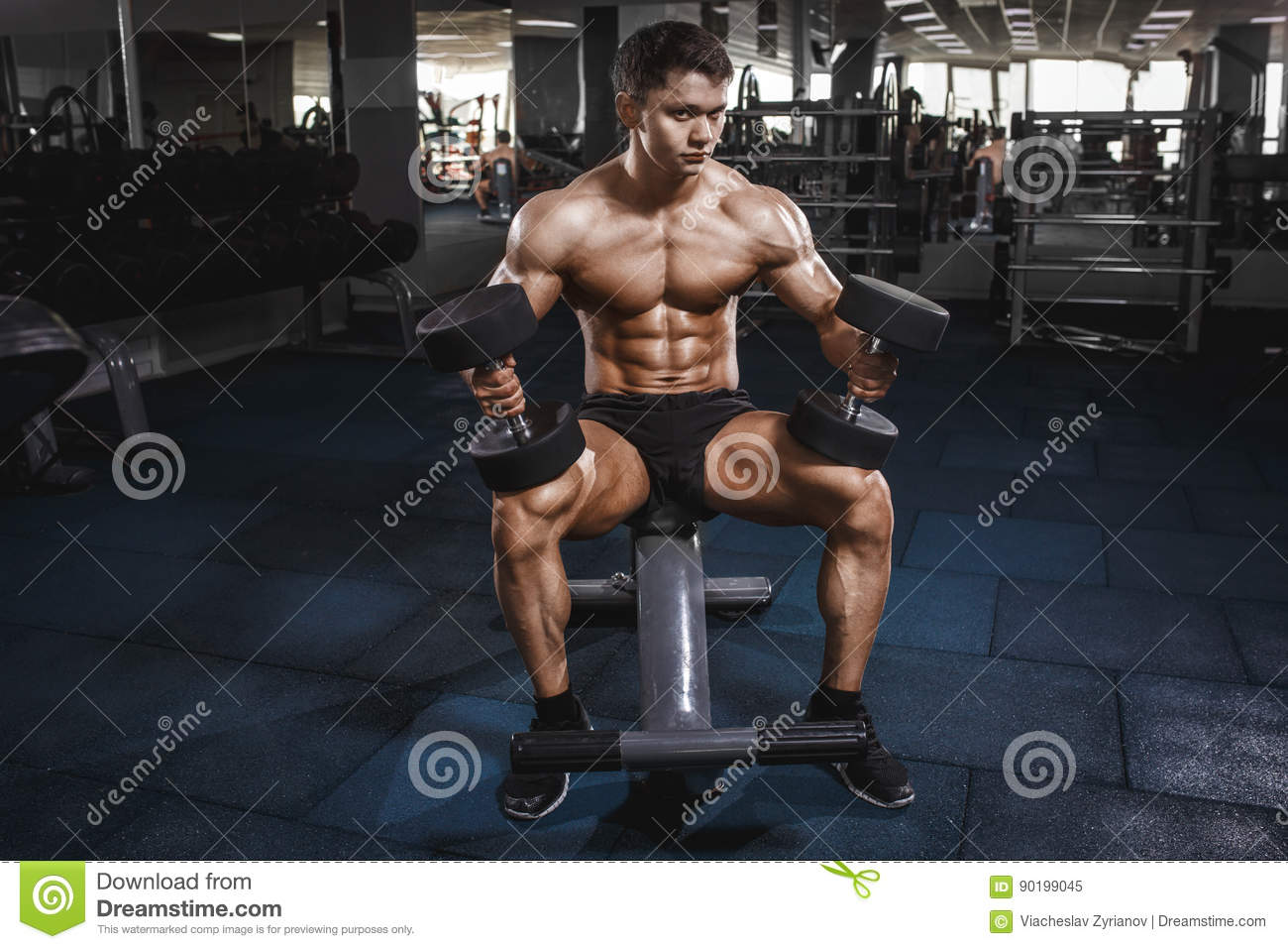 Athlete In The Gym Training With Dumbbells Stock Image