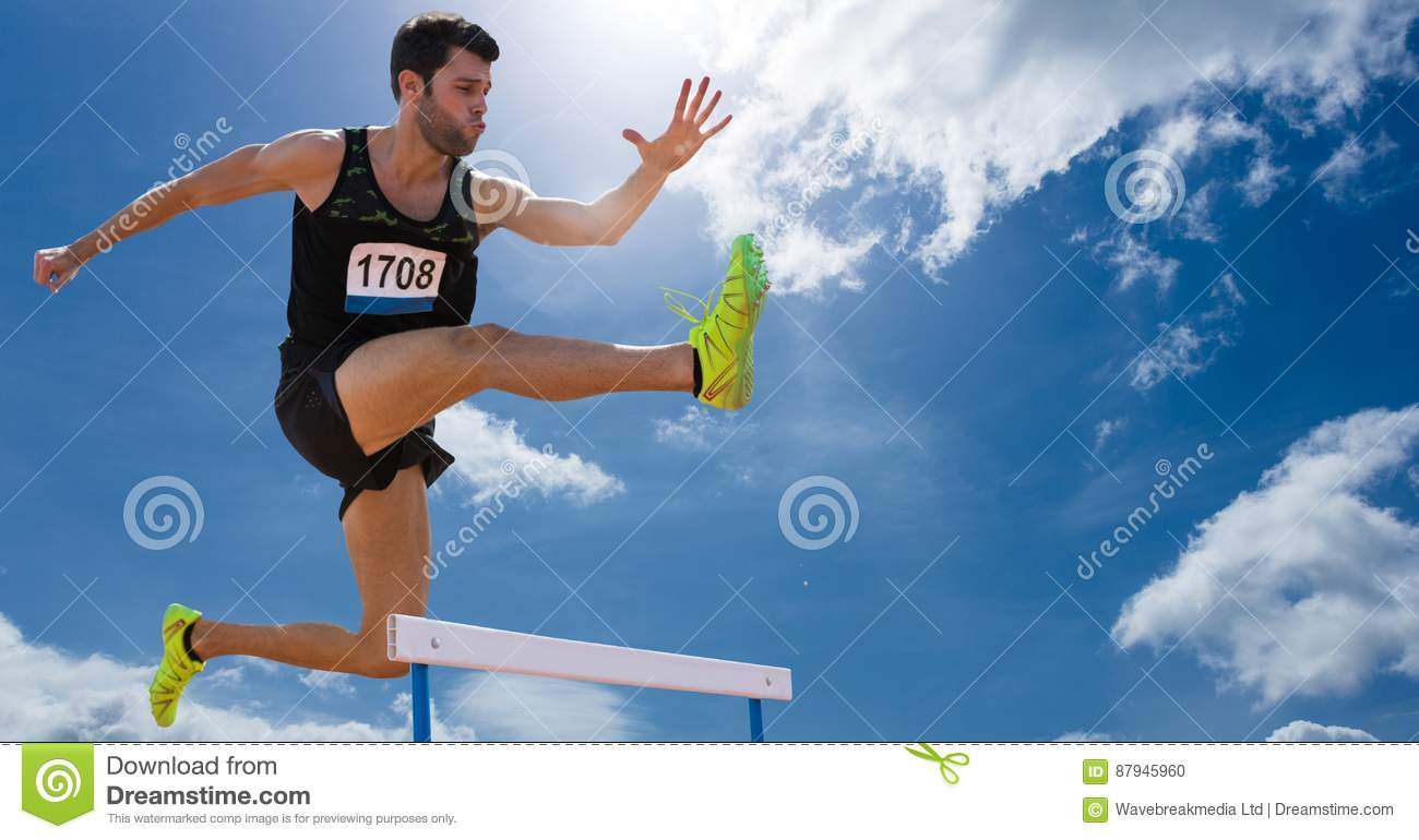 Athlete jumping over hurdles against sky in background