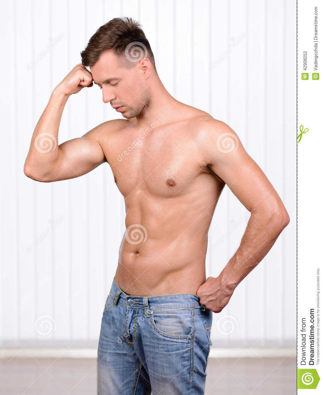 50b7713c5 Keeping his body in good shape. Cheerful young muscular man demonstration  of his body