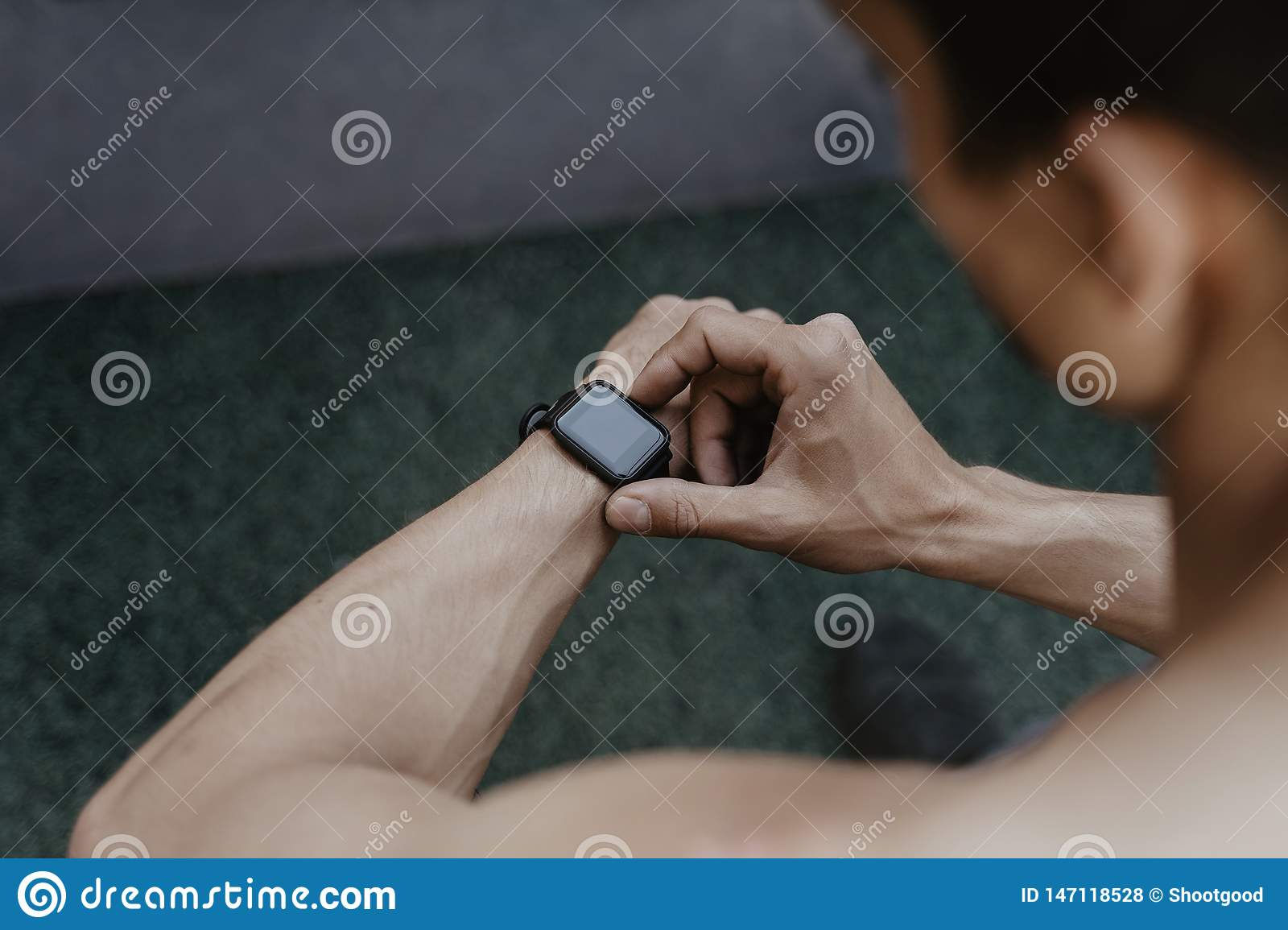 Athlete looking at his smartwatch fitness app after workout
