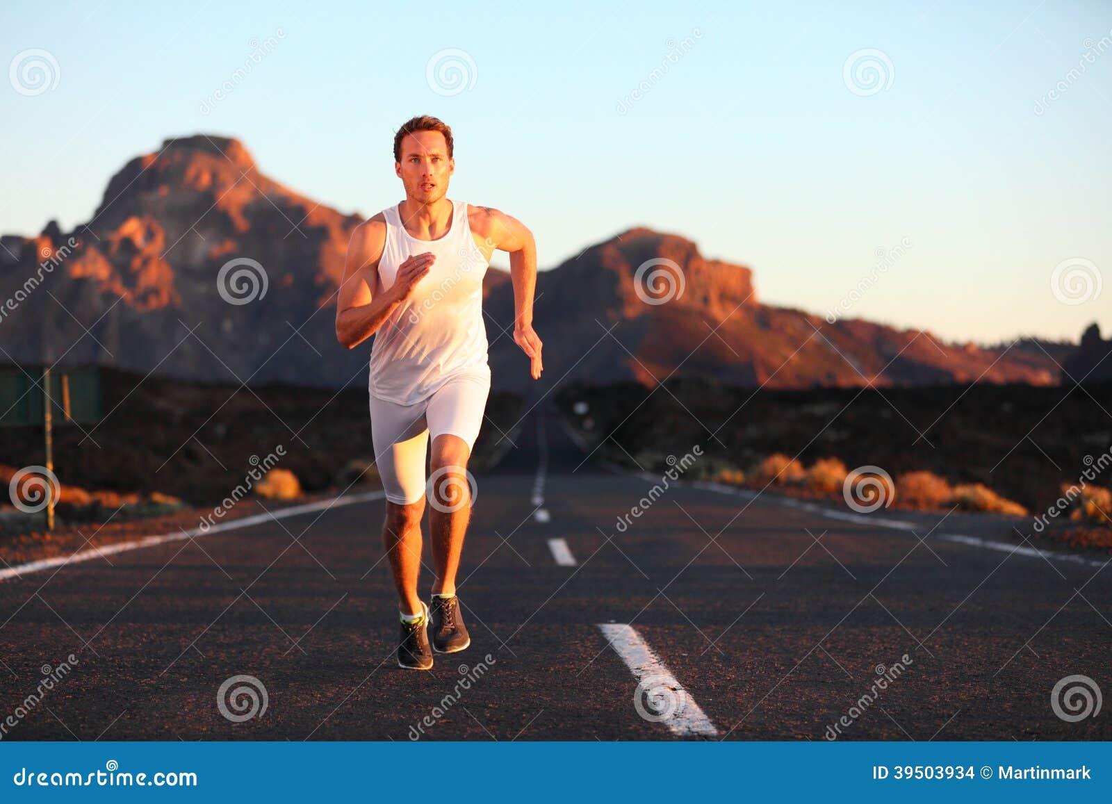 Athlete running sprinting at sunset on road