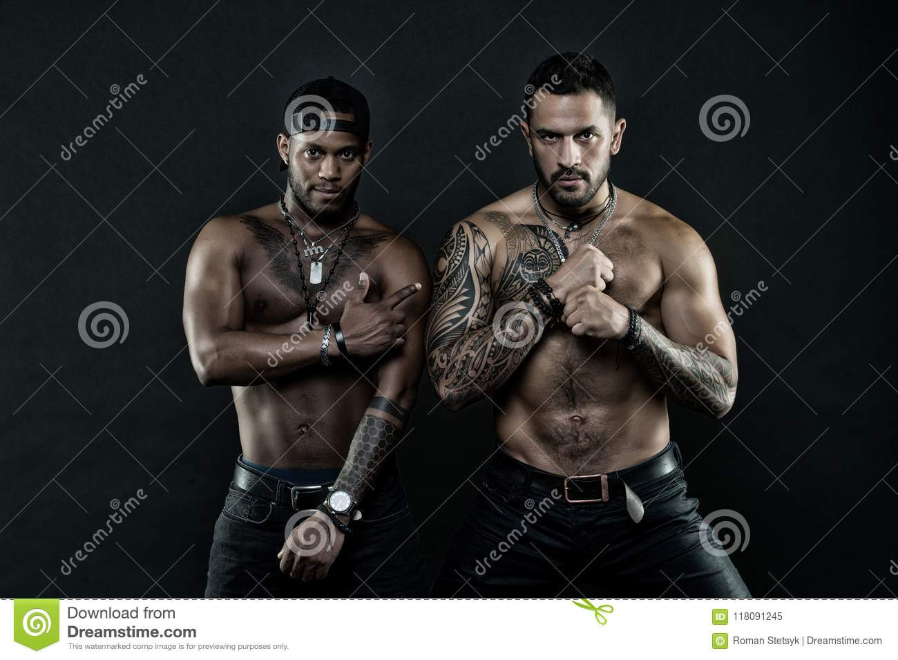 Athletes on confident faces with nude muscular chests and biceps. Machos with muscular tattooed torsos look attractive