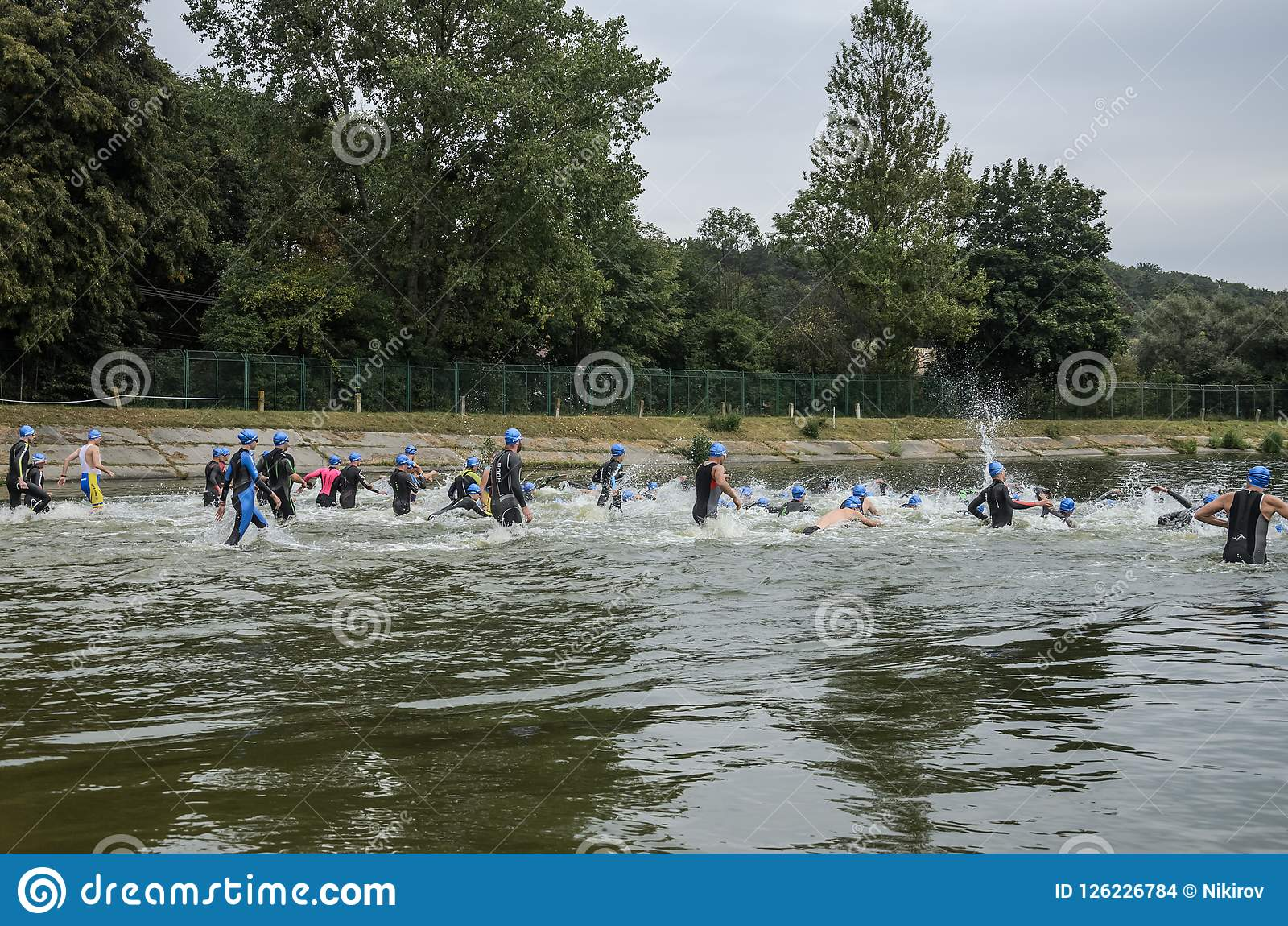UKRAINE, LVIV - SEPTEMBER 2018: Athletes in wetsuits at the start run into the water for a swim in the triathlon competition