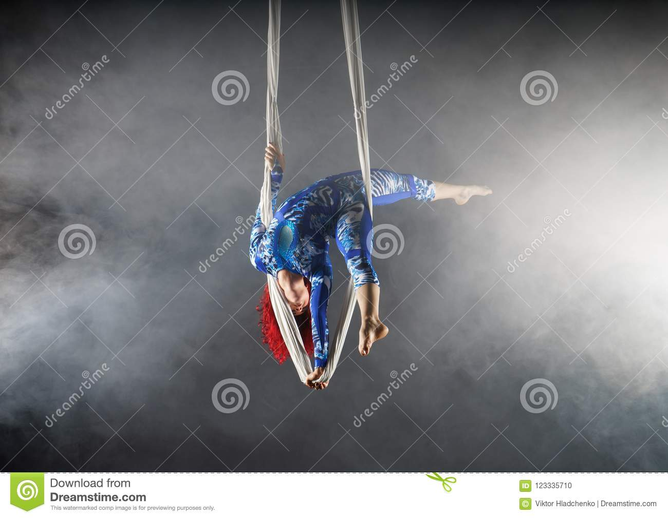 Athletic aerial circus artist with redhead in blue costume standing on one hand in the aerial silk