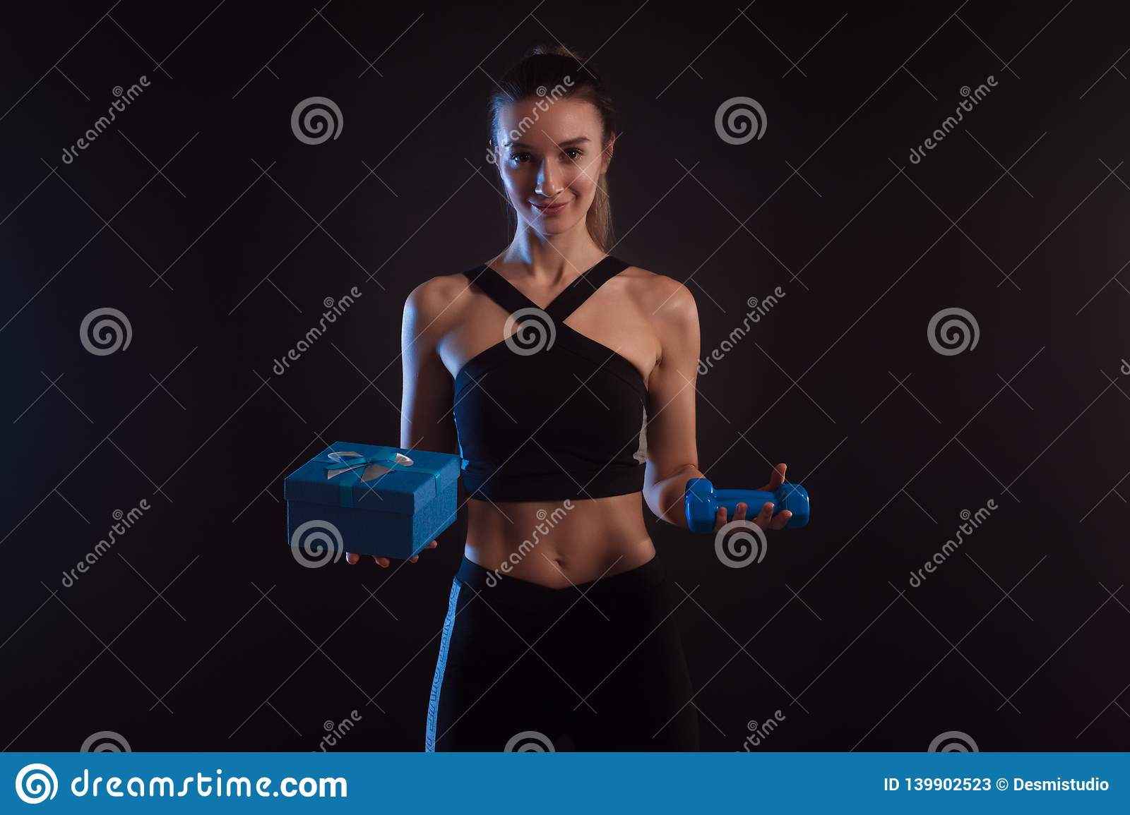 Athletic blonde holding dumbbells and gift box in her hands