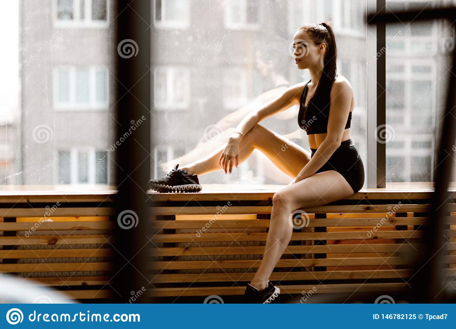 Athletic dark-haired girl dressed in black sports top and shorts is sitting on a wooden window sill in the gym