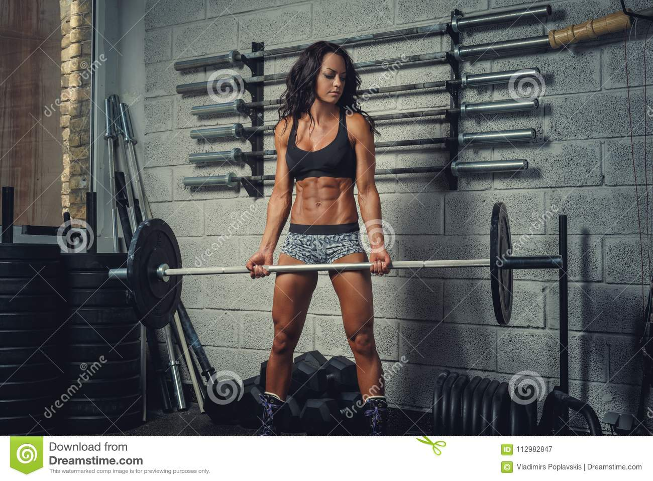 Athletic female holding barbell.