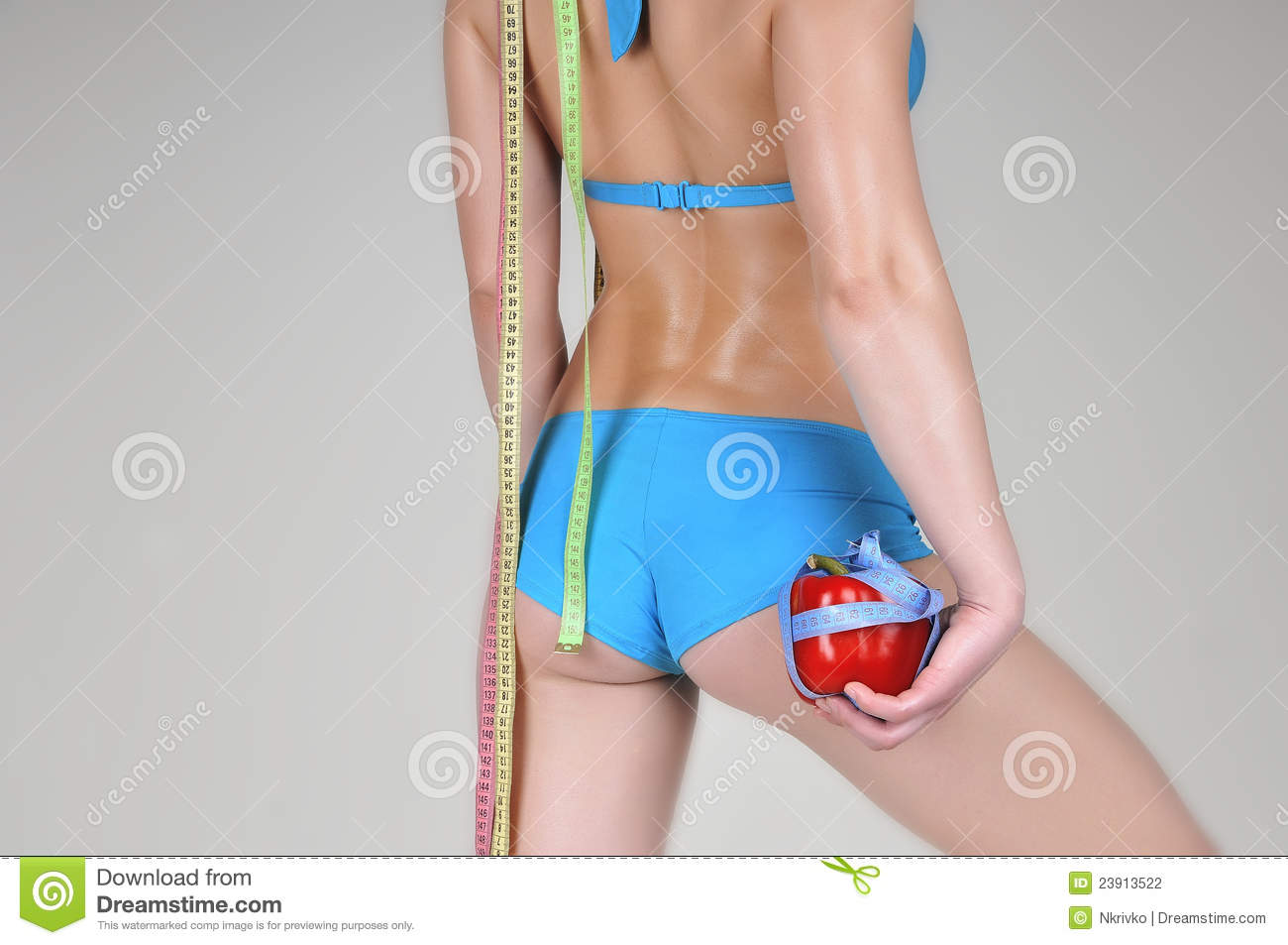 Athletic girl in a blue swimsuit with red pepper