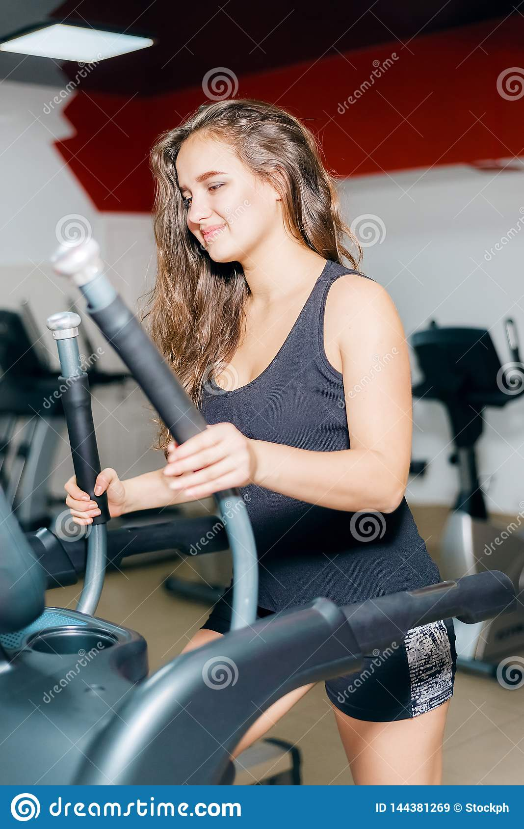 Athletic girl trains cardio on the stepper simulator. woman in the gym smiling