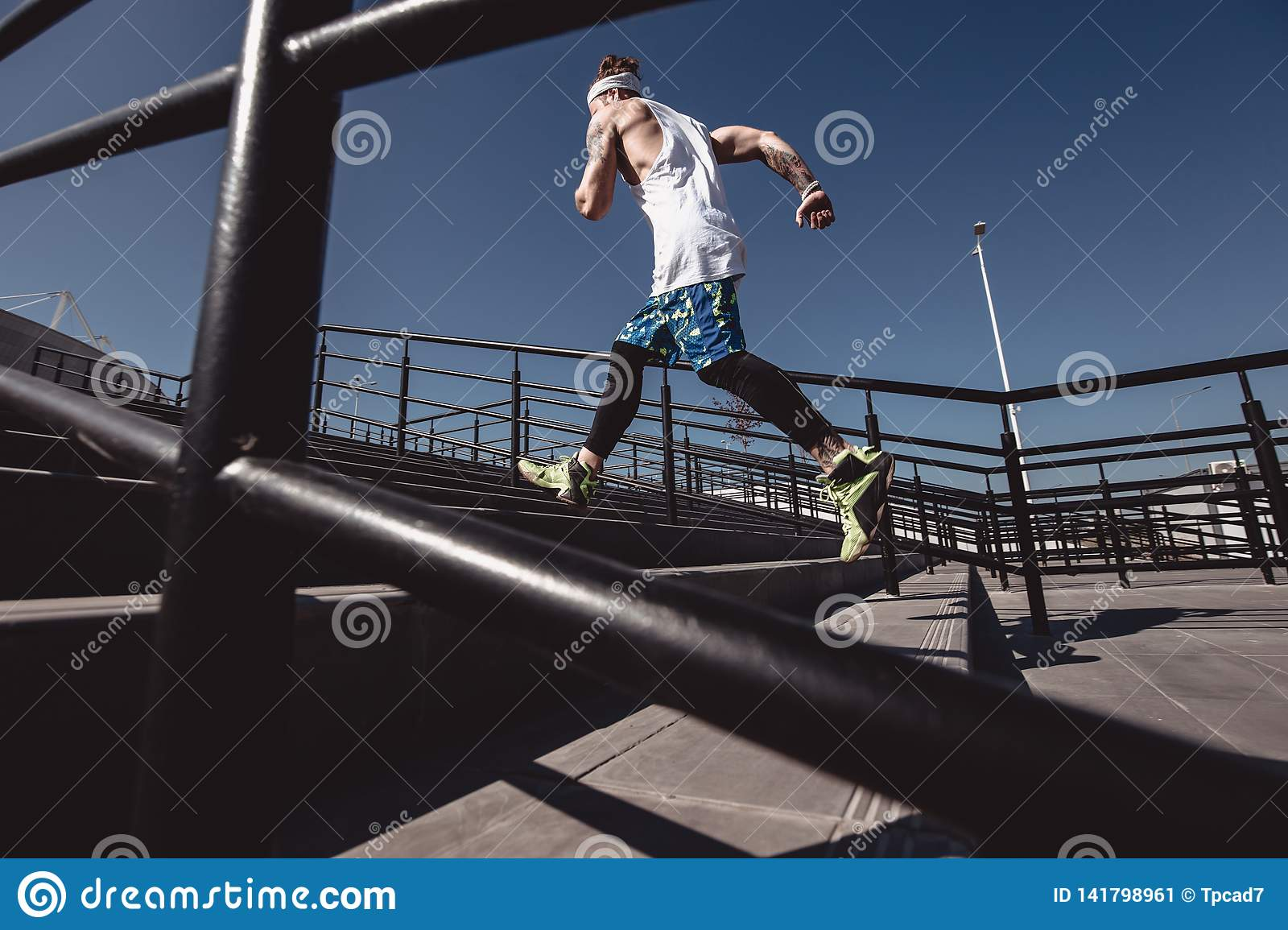 Athletic man with headband on his head dressed in the white t-shirt, black leggings and blue shorts is running up the
